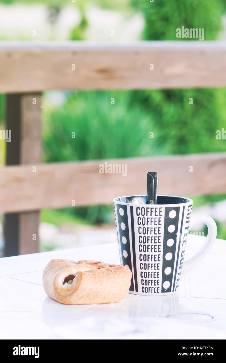 La Veranda Di Campagna una tazza di caffè con un cornetto sul tavolo, la veranda di