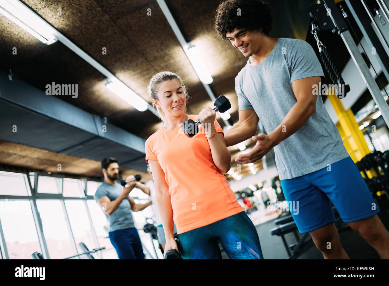 Giovane bella donna facendo esercizi con personal trainer Immagini Stock