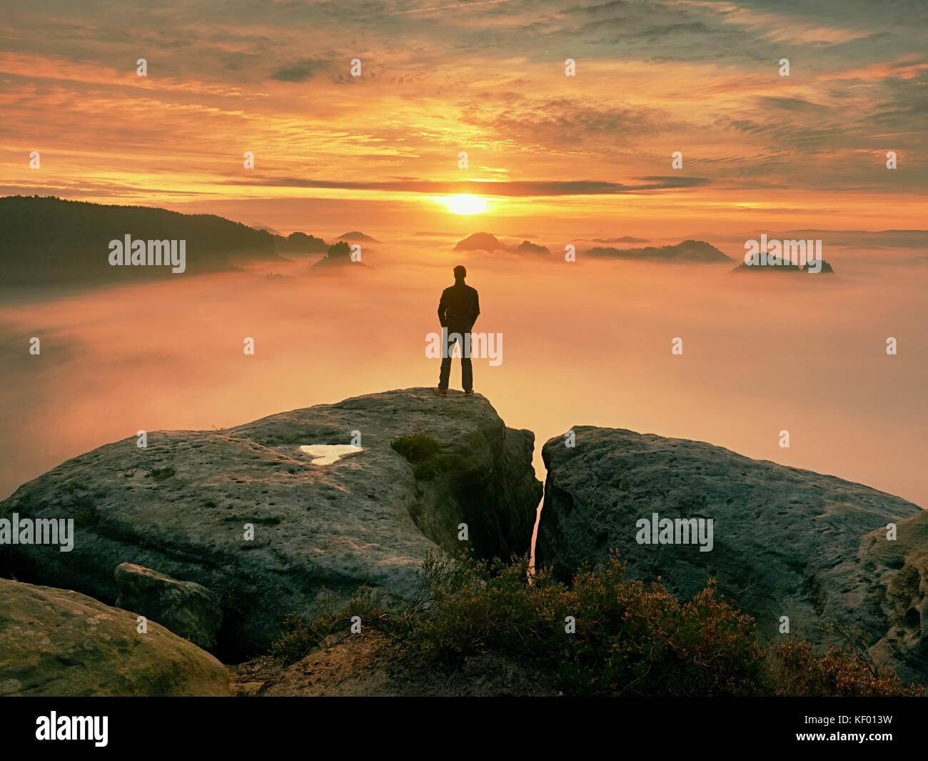 L'uomo si trova solo sul picco di roccia. escursionista guardando al sole autunnale all orizzonte . bel momento Immagini Stock