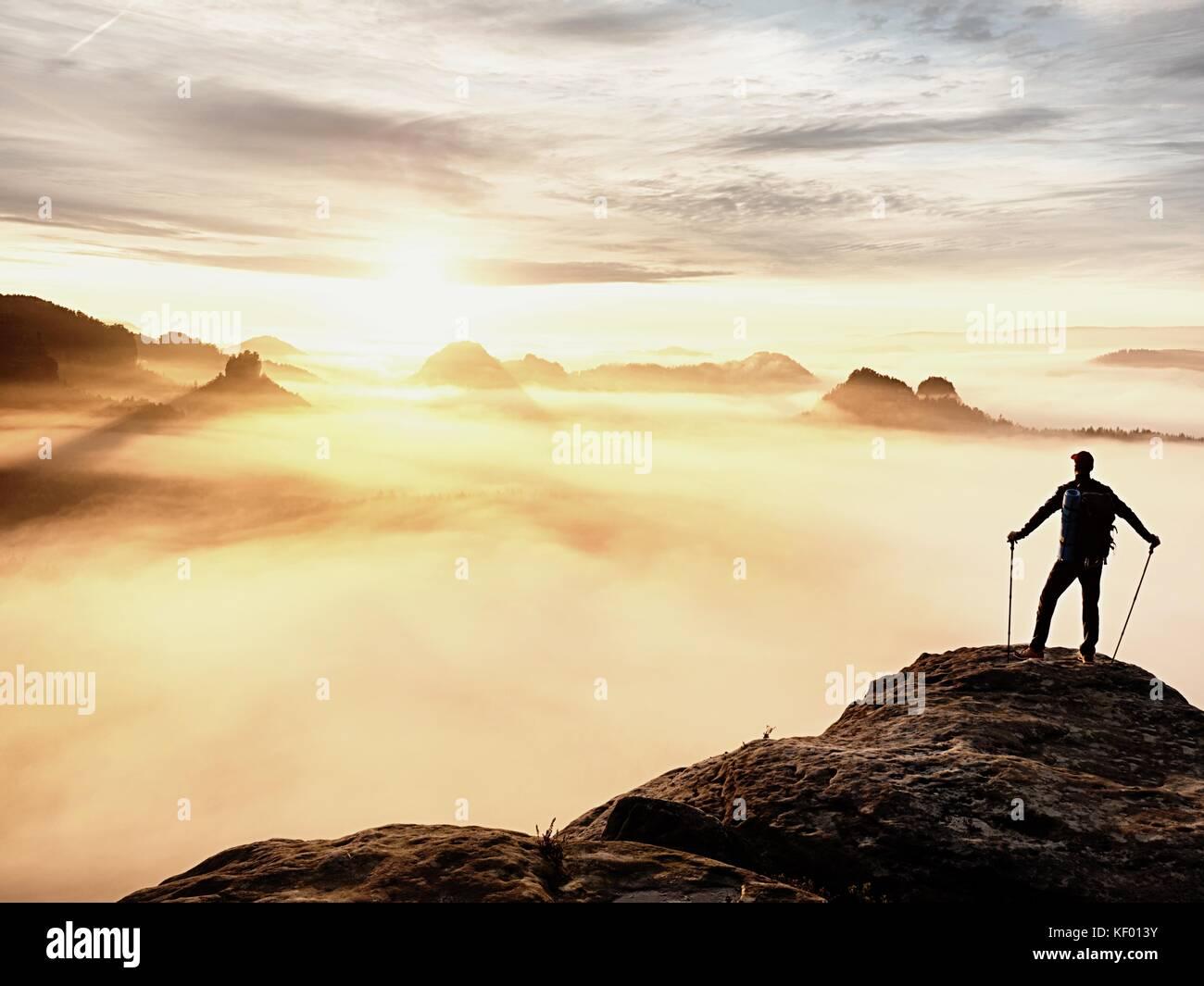 Silhouette uomo con pali in mano. primavera soleggiata lo spuntar del giorno e guida turistica soggiorno su sharp Immagini Stock