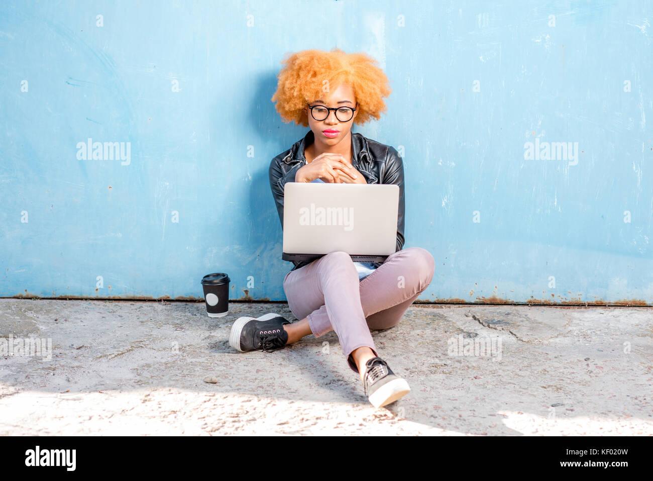 Donna africana con il portatile su sfondo blu Foto Stock