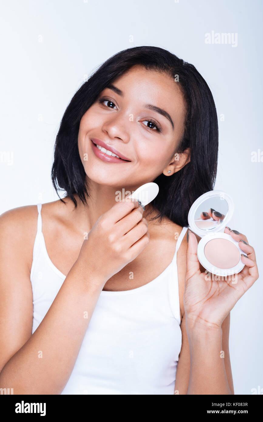 Sorridente giovane donna l'applicazione di polvere con un soffio Foto Stock