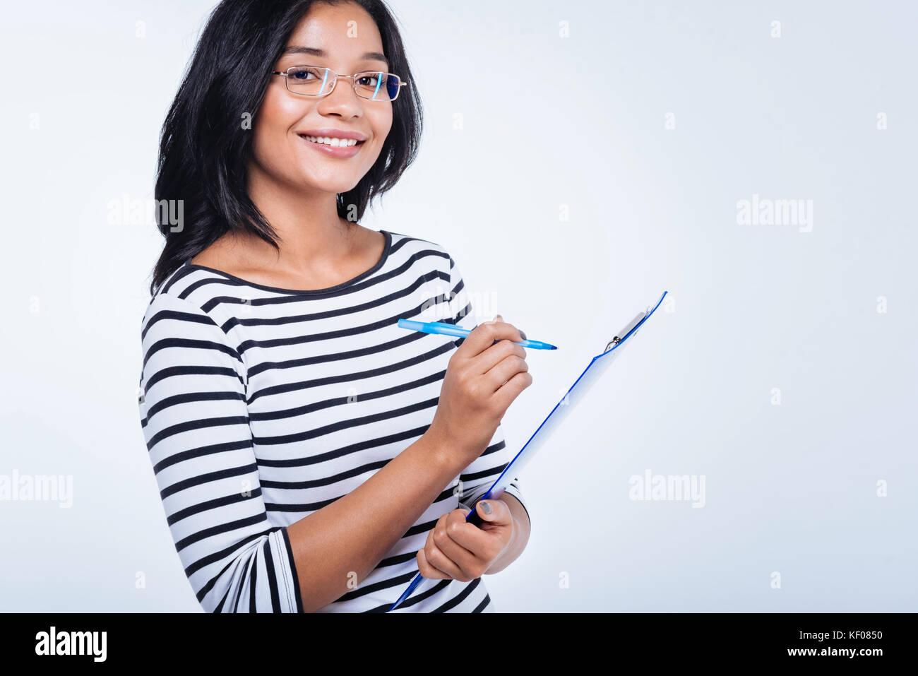 Donna allegra rendendo note sul foglio imperniata al supporto Immagini Stock