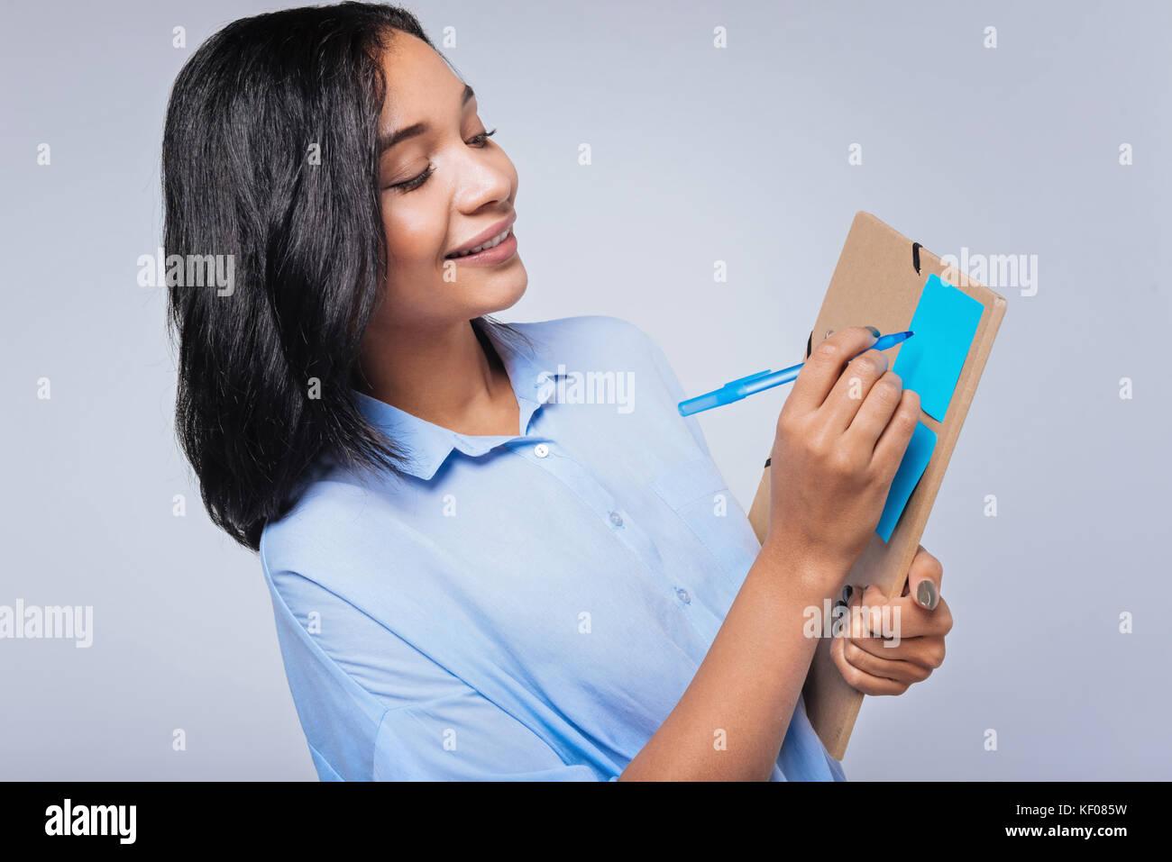 Piacevole dai capelli scuri scrittura donna su un foglietto adesivo Immagini Stock
