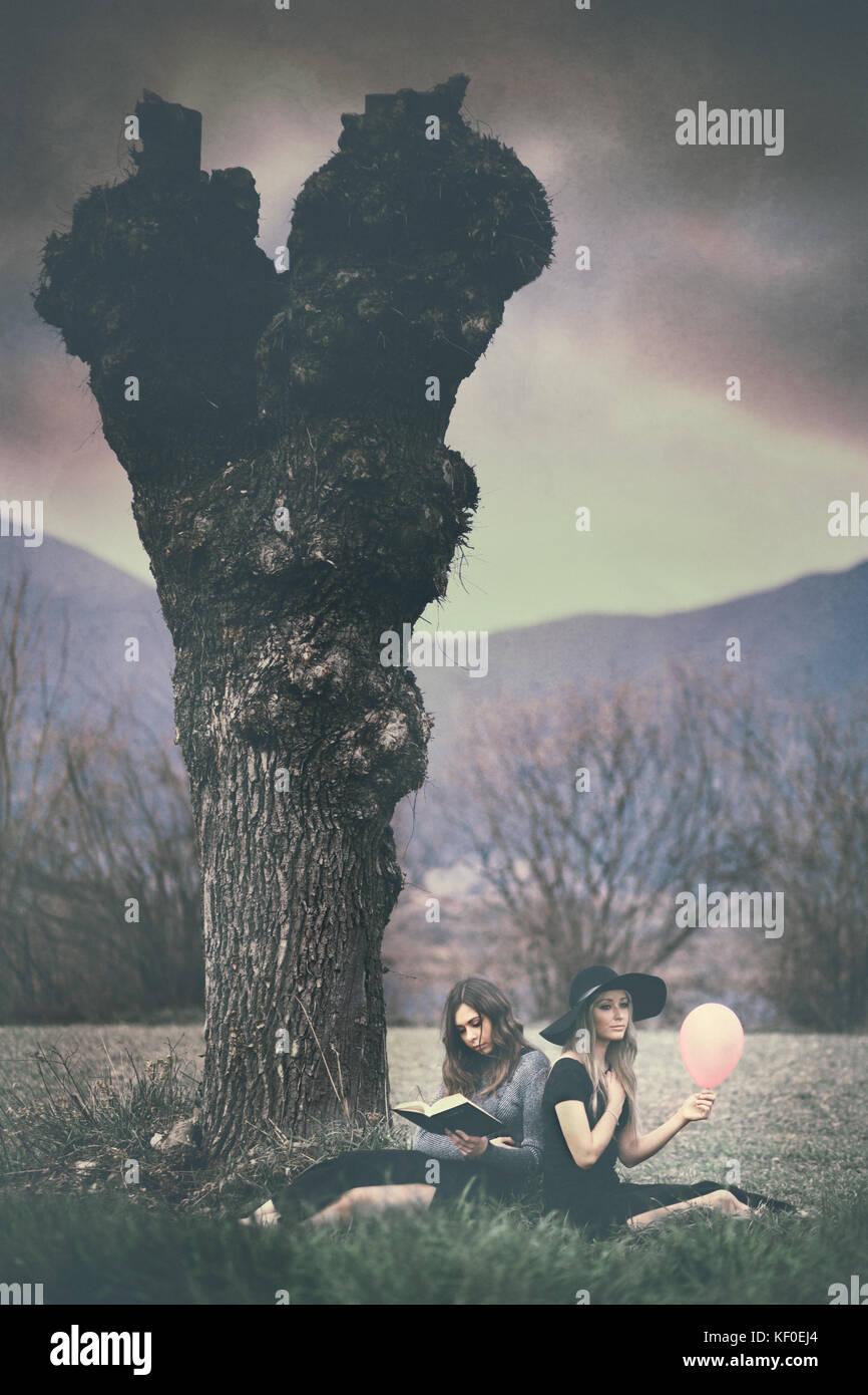 Opposti: due ragazze seduto sotto un albero, uno tenendo un palloncino rosa, l'altra in possesso di un libro Immagini Stock