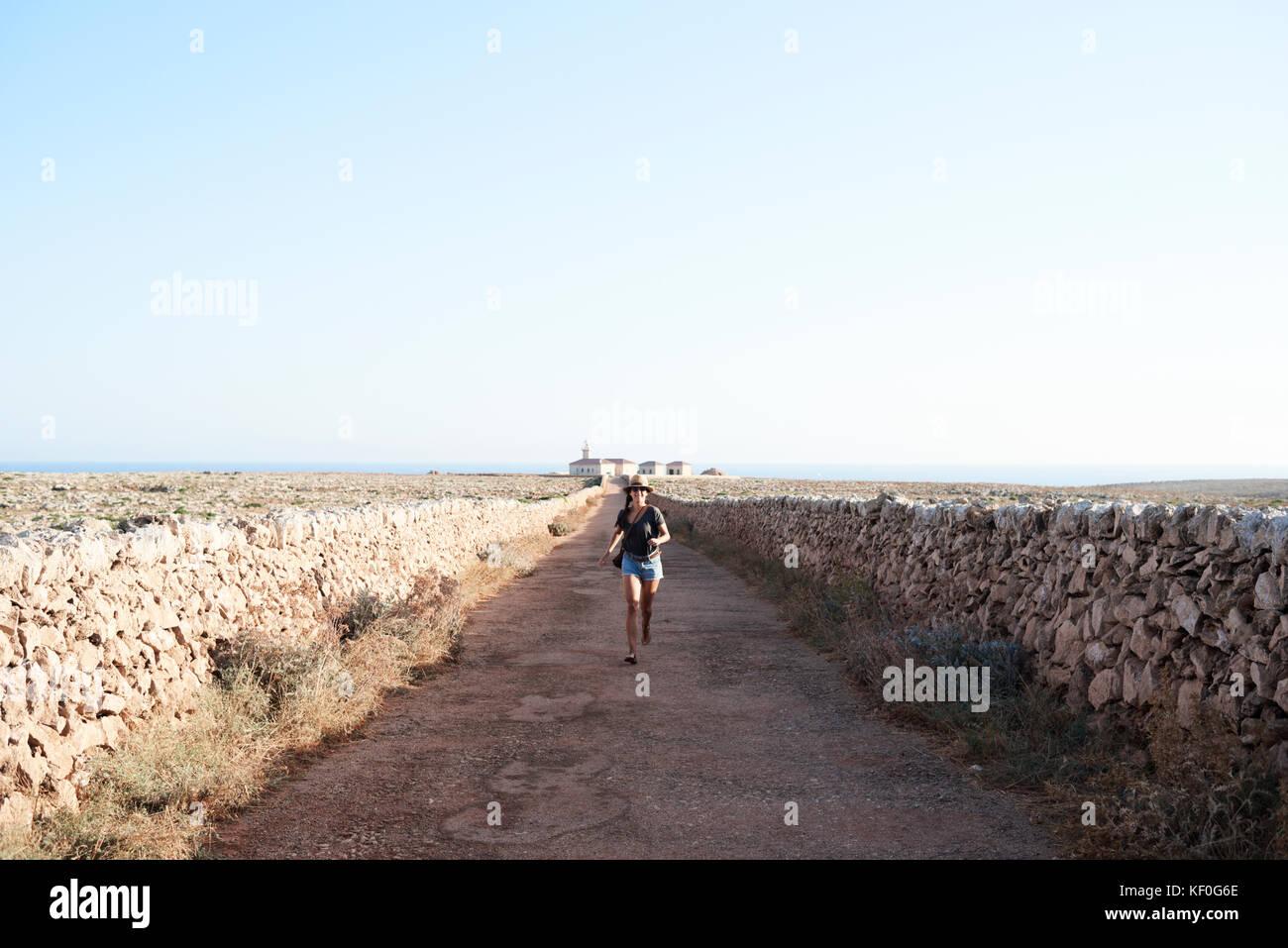 Menorca, Spagna, felice solo traveler in esecuzione in una strada vuota per un faro in Minorca, solo traveler Immagini Stock