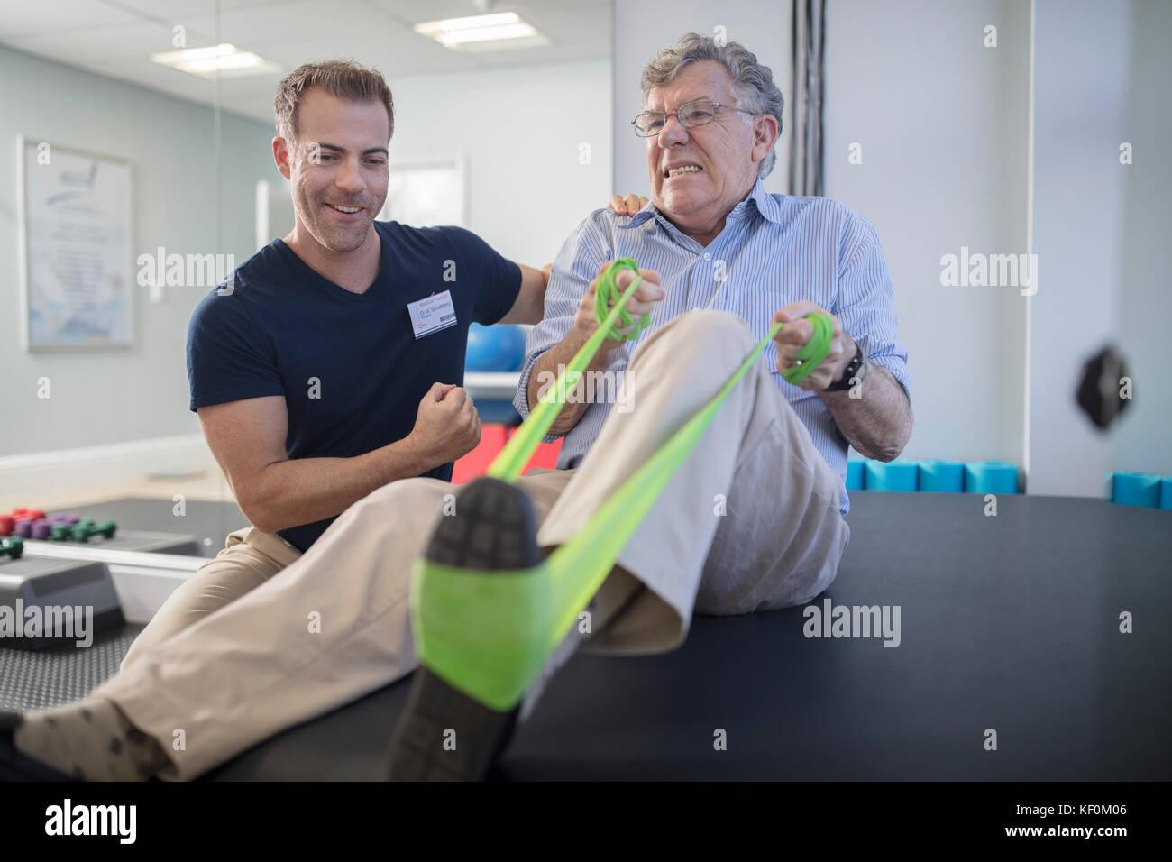 Senior uomo esercitando con resistenza a fascia physio in pratica Immagini Stock
