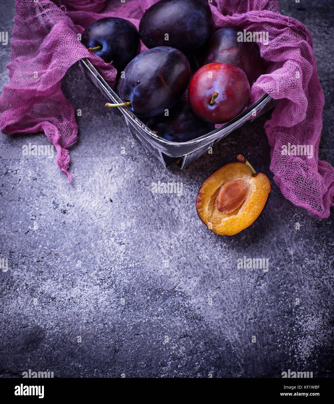 Fresche dolci prugne su sfondo di calcestruzzo Immagini Stock