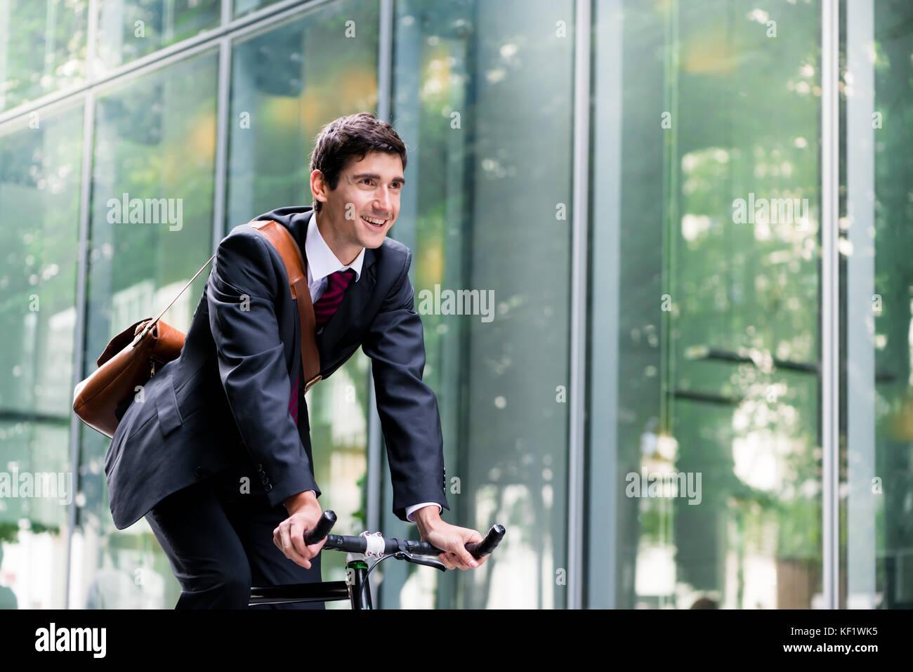 Allegro giovane lavoratore in sella ad una bicicletta di utilità a Berlino Immagini Stock