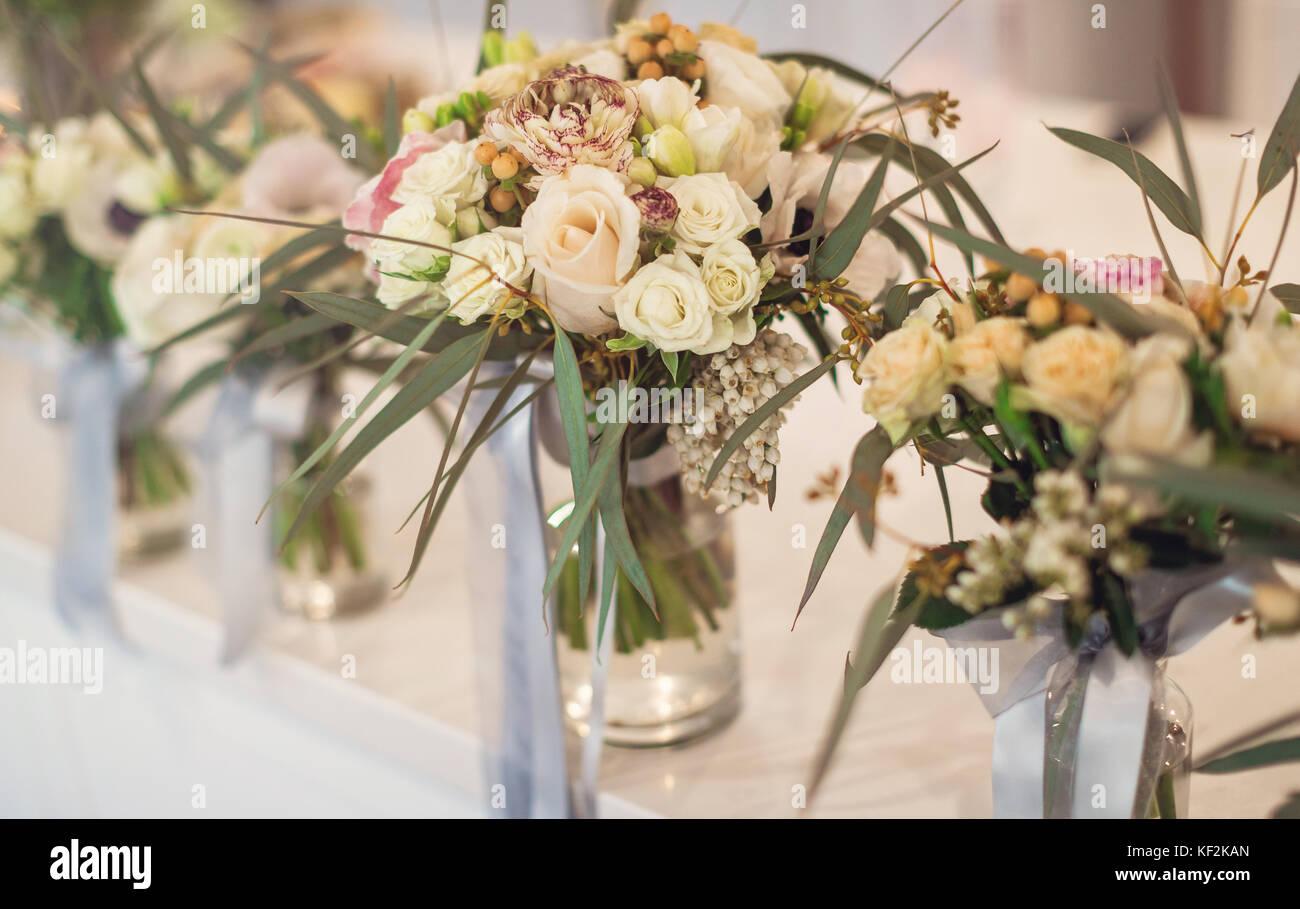 6fd7644e0c3f Fiori di matrimonio per la festa nuziale con archetti e nastri in bottiglie  trasparenti con acqua in esso