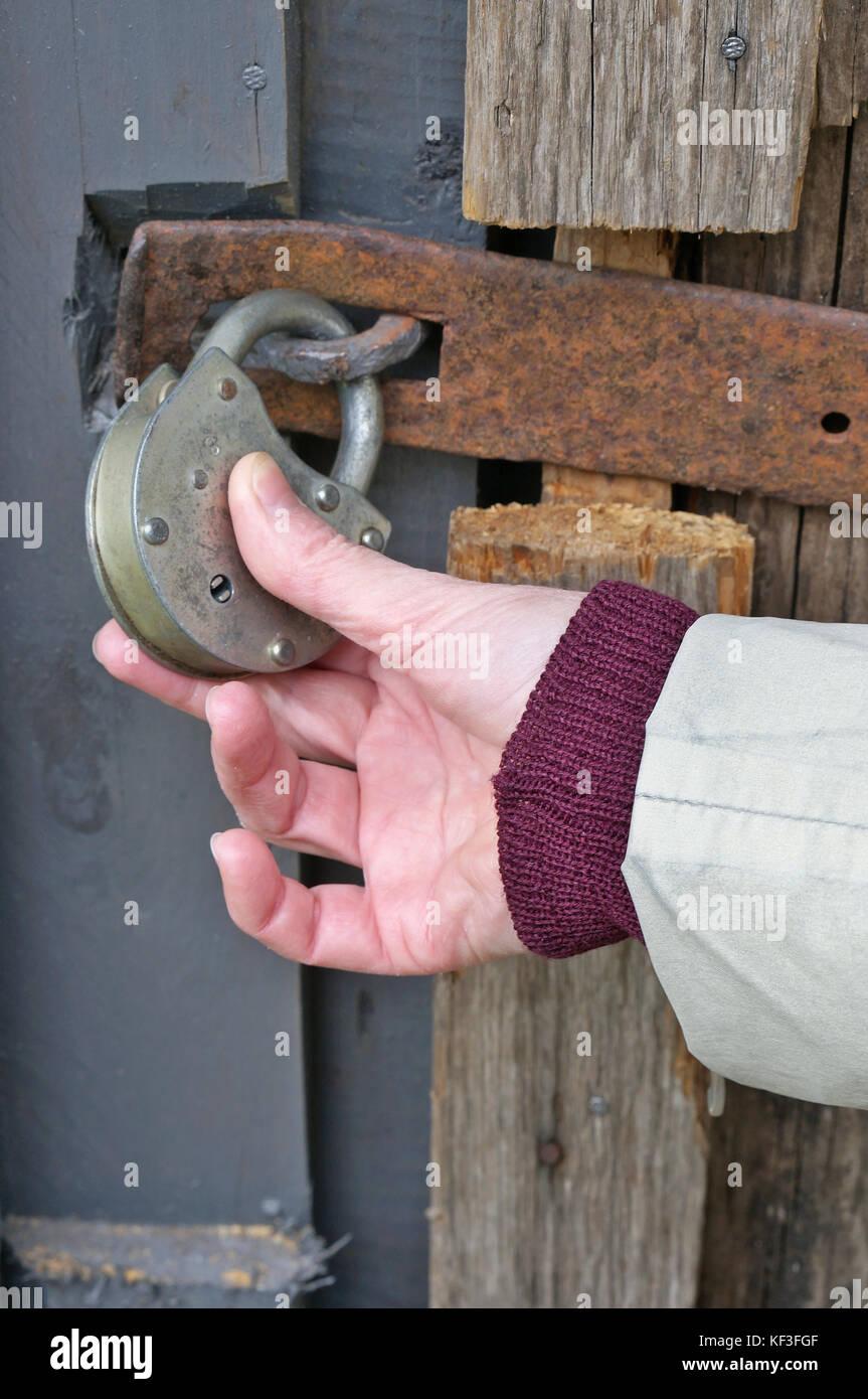 La mano di un anziana donna di villaggio detiene una serratura chiusa sulla  porta di 406b4f536b6e