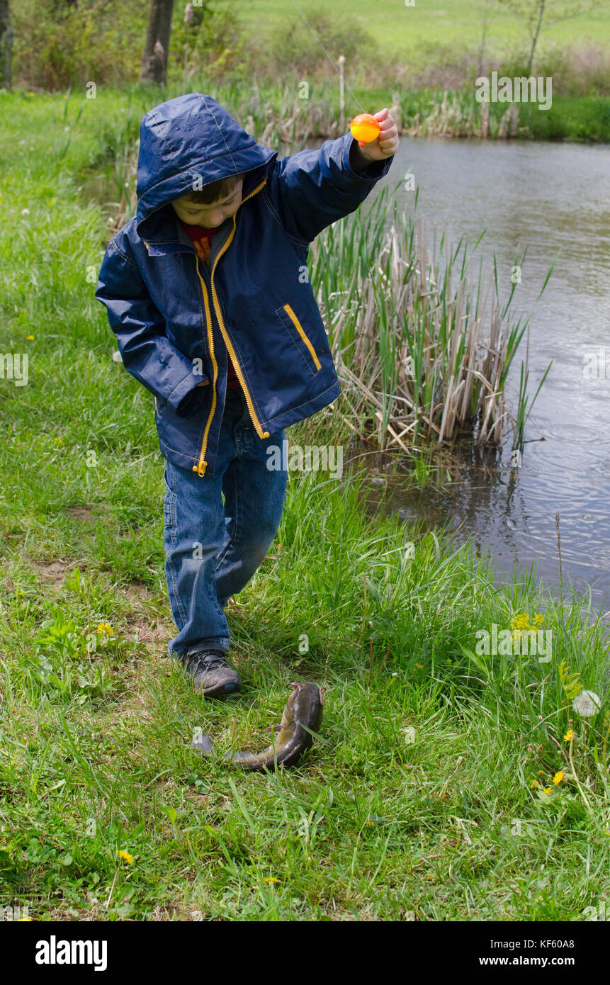 5-6 anno vecchio ragazzo di pesca da uno stagno in estate. Foto Stock
