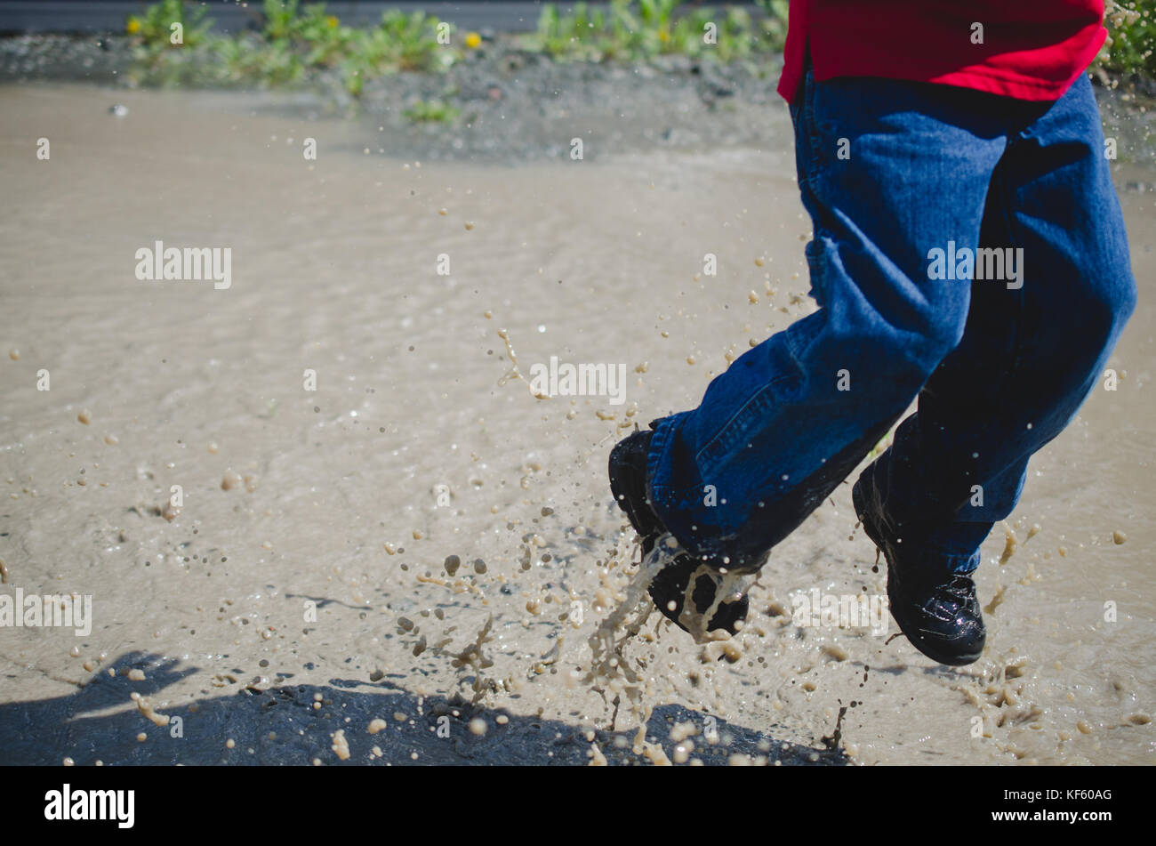 Bambino di saltare in una pozza di fango solo piedi Immagini Stock