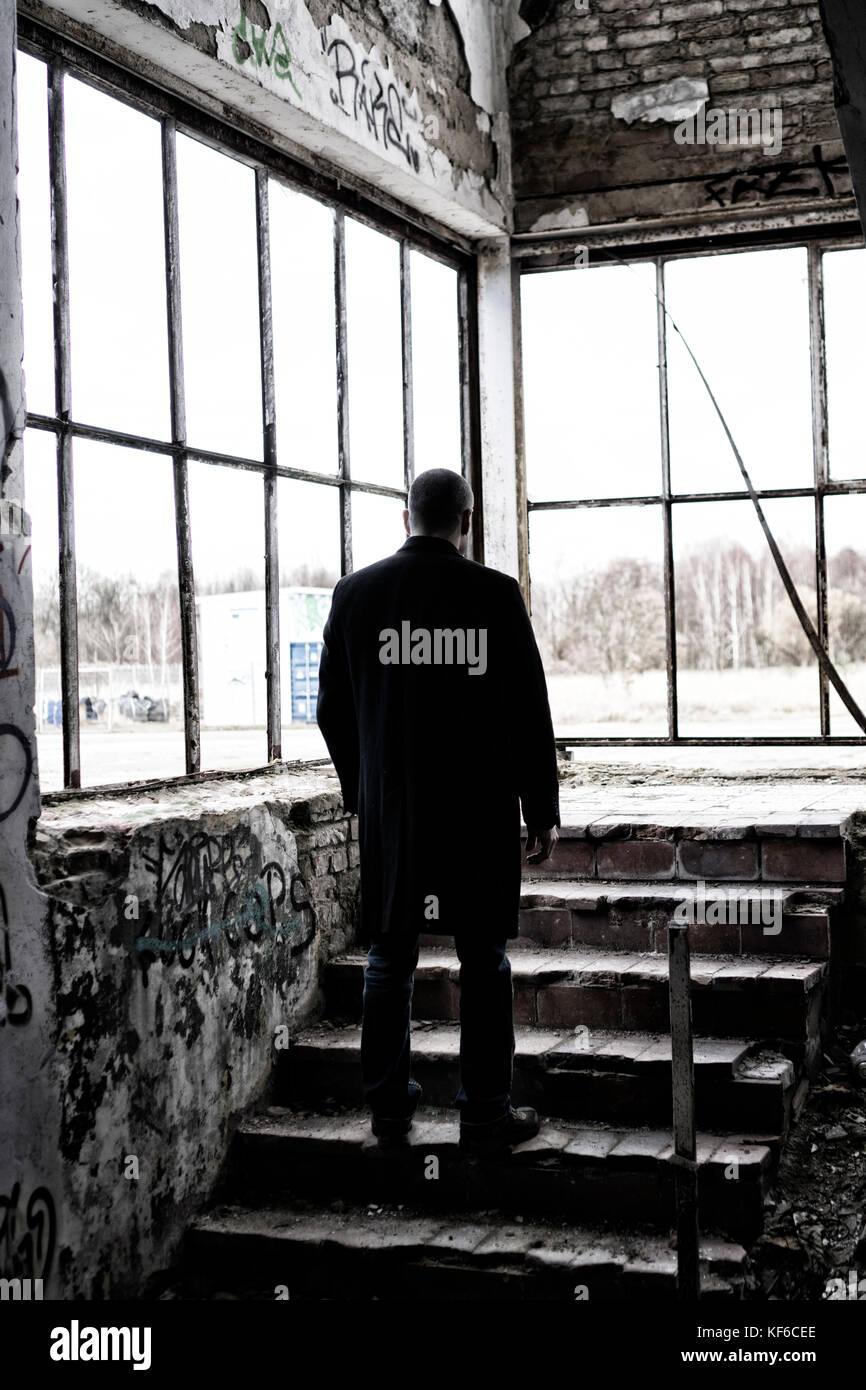 Vista posteriore di una misteriosa figura maschile in piedi sui gradini all'interno di un edificio abbandonato Immagini Stock