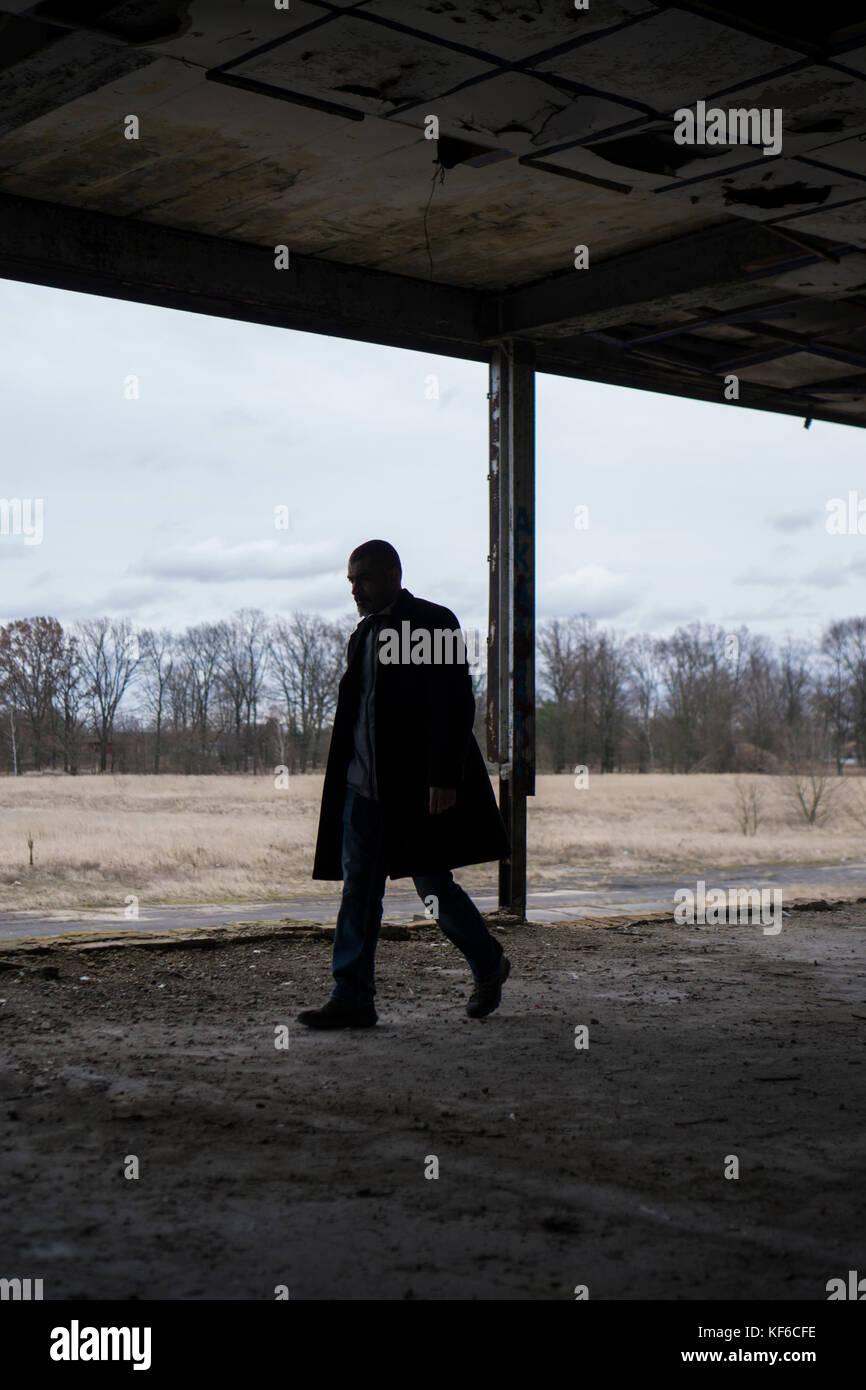 Vista laterale di un uomo che indossa un cappotto camminando all'interno di un edificio abbandonato Immagini Stock