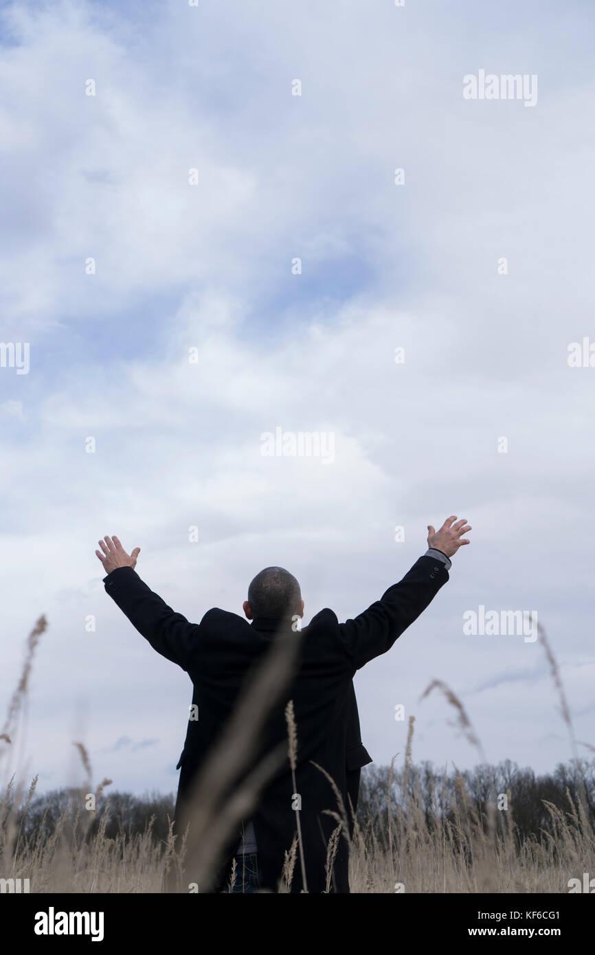 Vista posteriore di un uomo che indossa un cappotto in piedi un campo braccia tese Immagini Stock