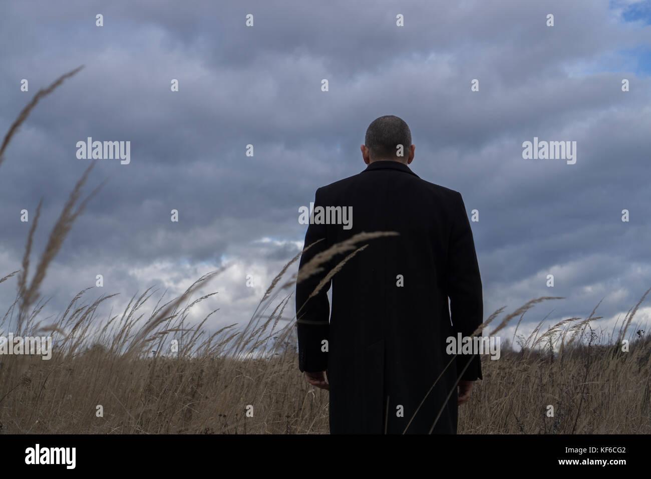Vista posteriore di un uomo che indossa un cappotto in piedi in un campo con cielo molto nuvoloso Immagini Stock
