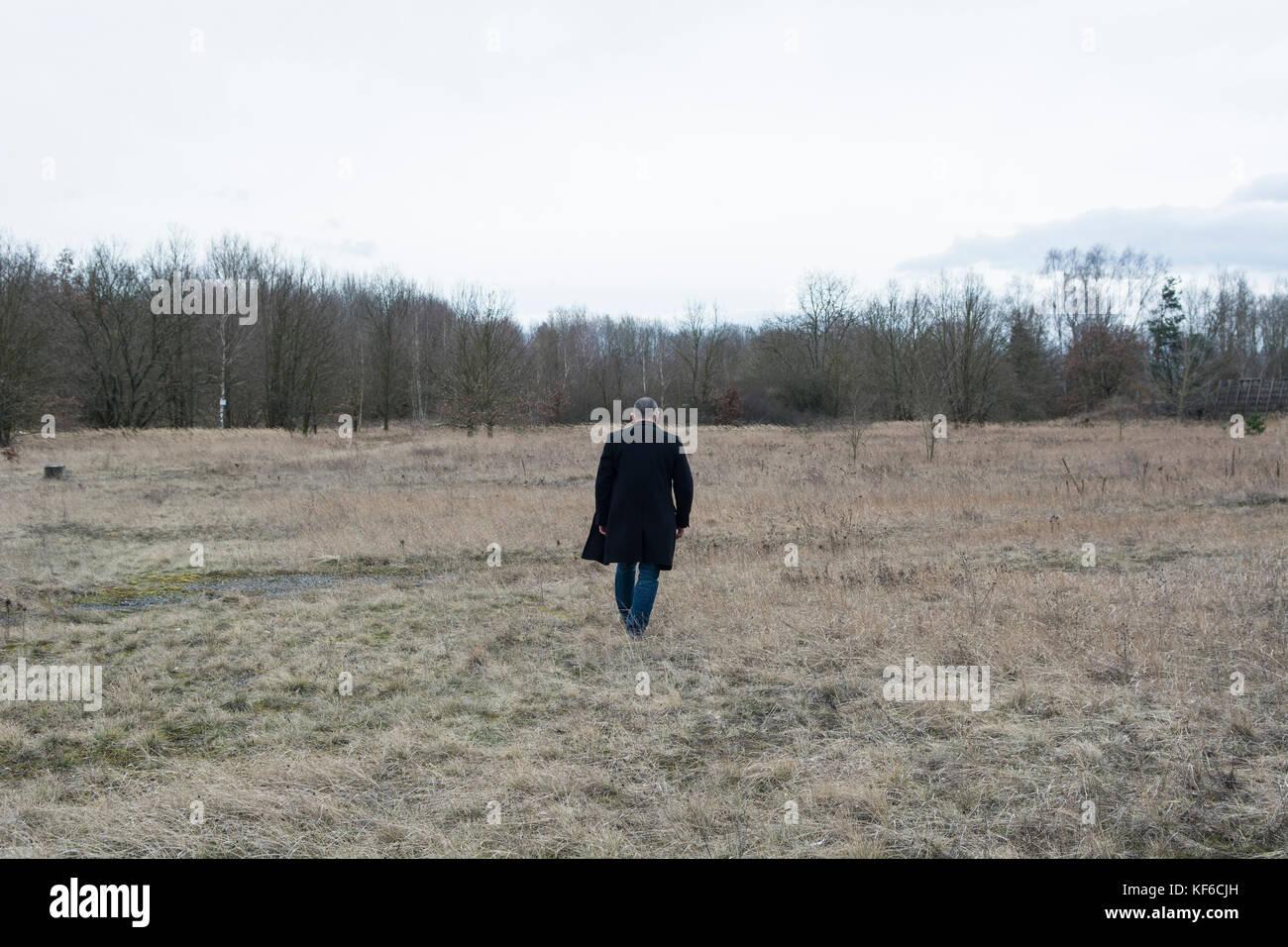 Vista posteriore schematica di un uomo che indossa un cappotto a piedi in un campo Immagini Stock
