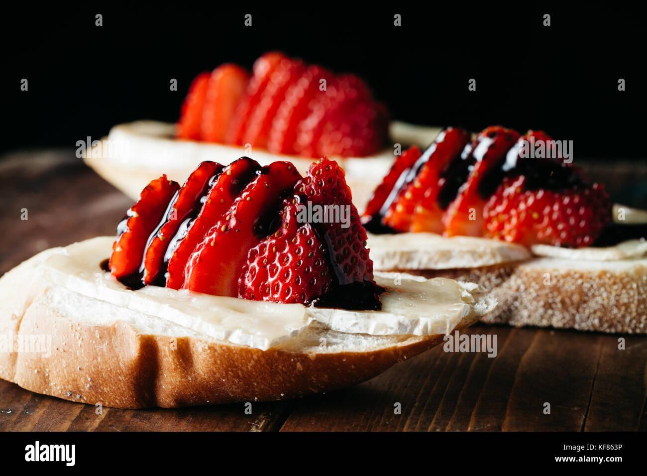 Crostini con formaggio brie, fragole fresche rustico superficie in legno Immagini Stock