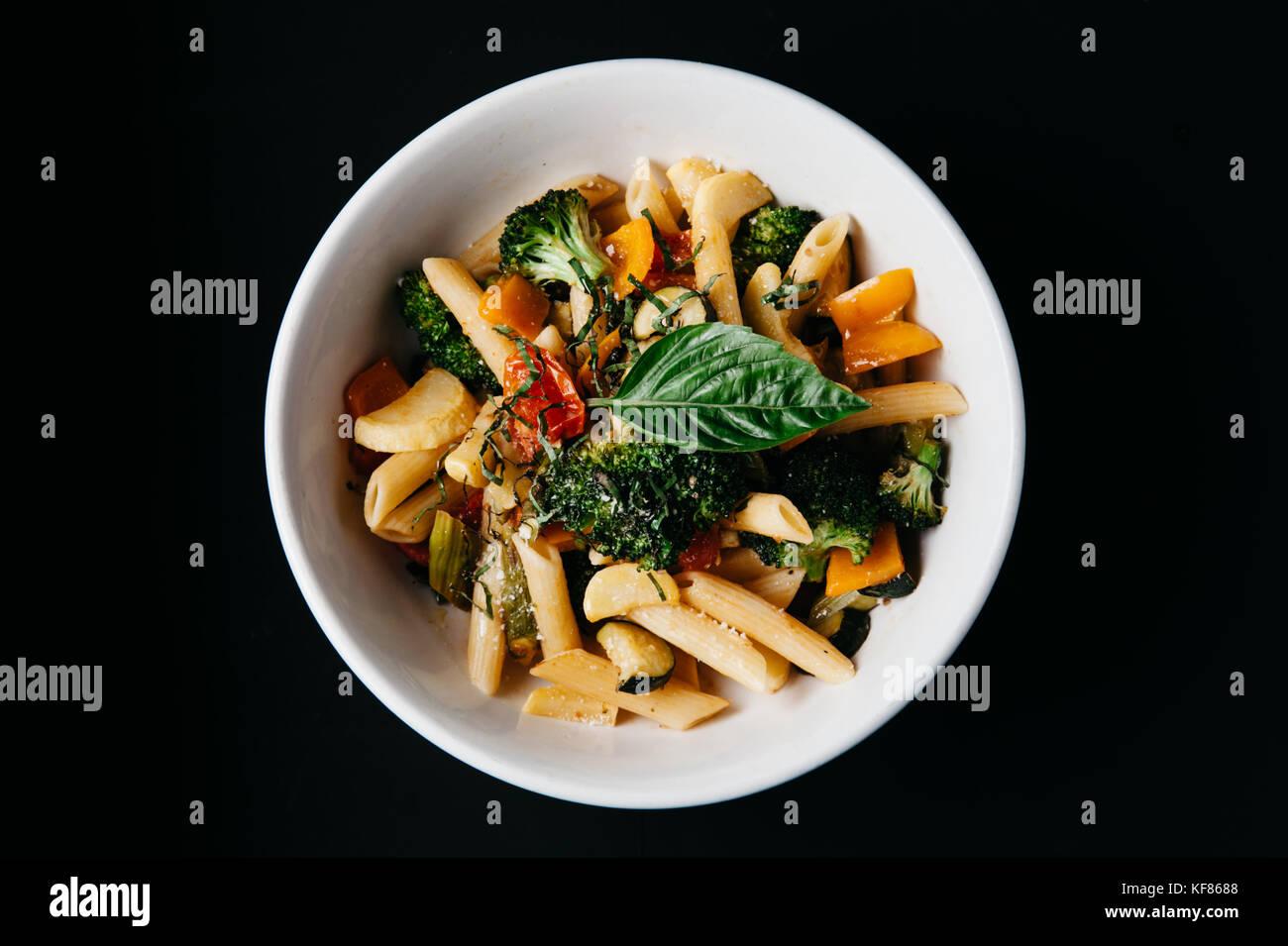Una piastra di penne con pomodoro fresco e basilico, broccoli con olio di oliva e il formaggio parmigiano reggiano Immagini Stock