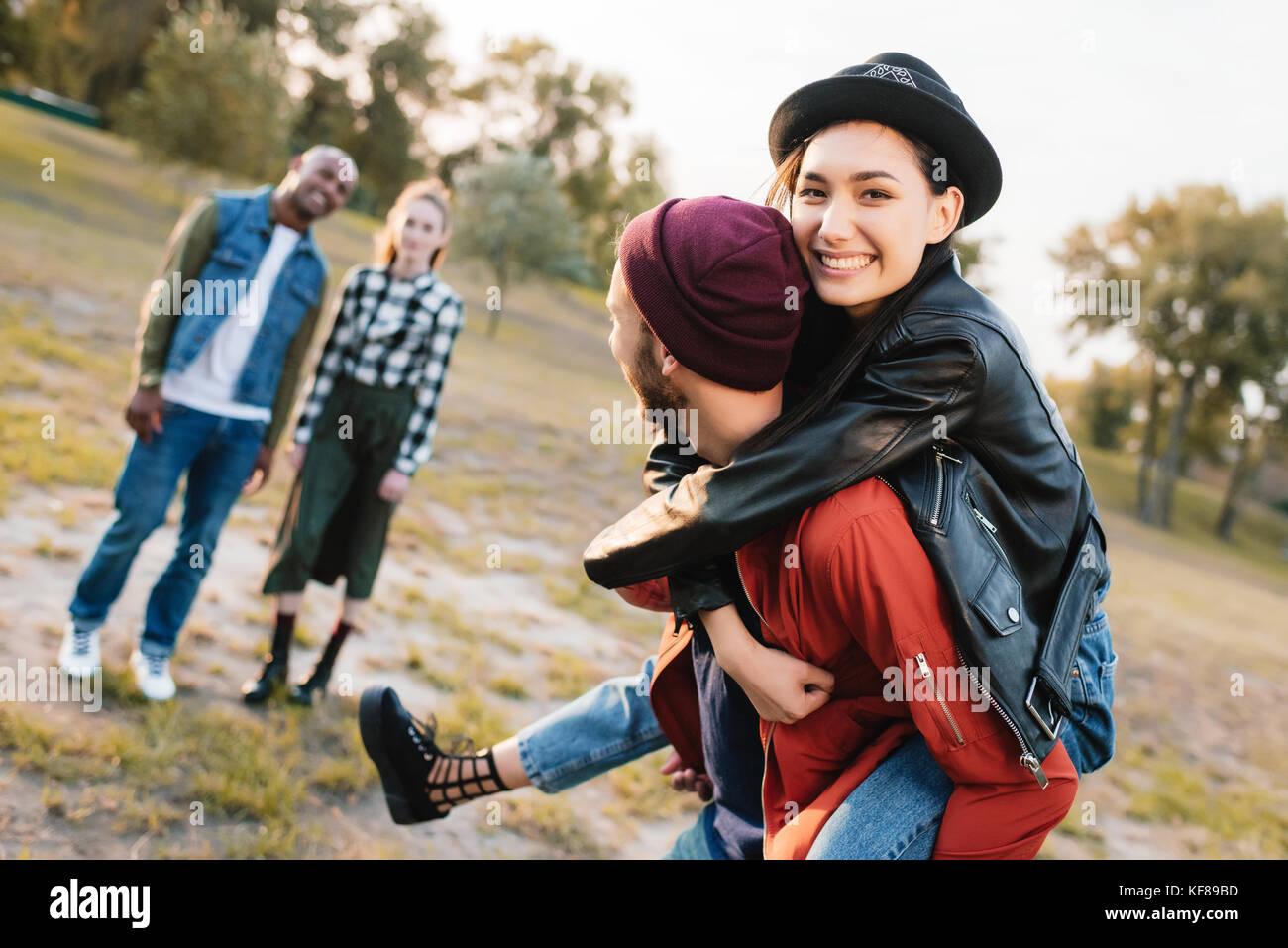 Giovane piggybacking in posizione di parcheggio Immagini Stock
