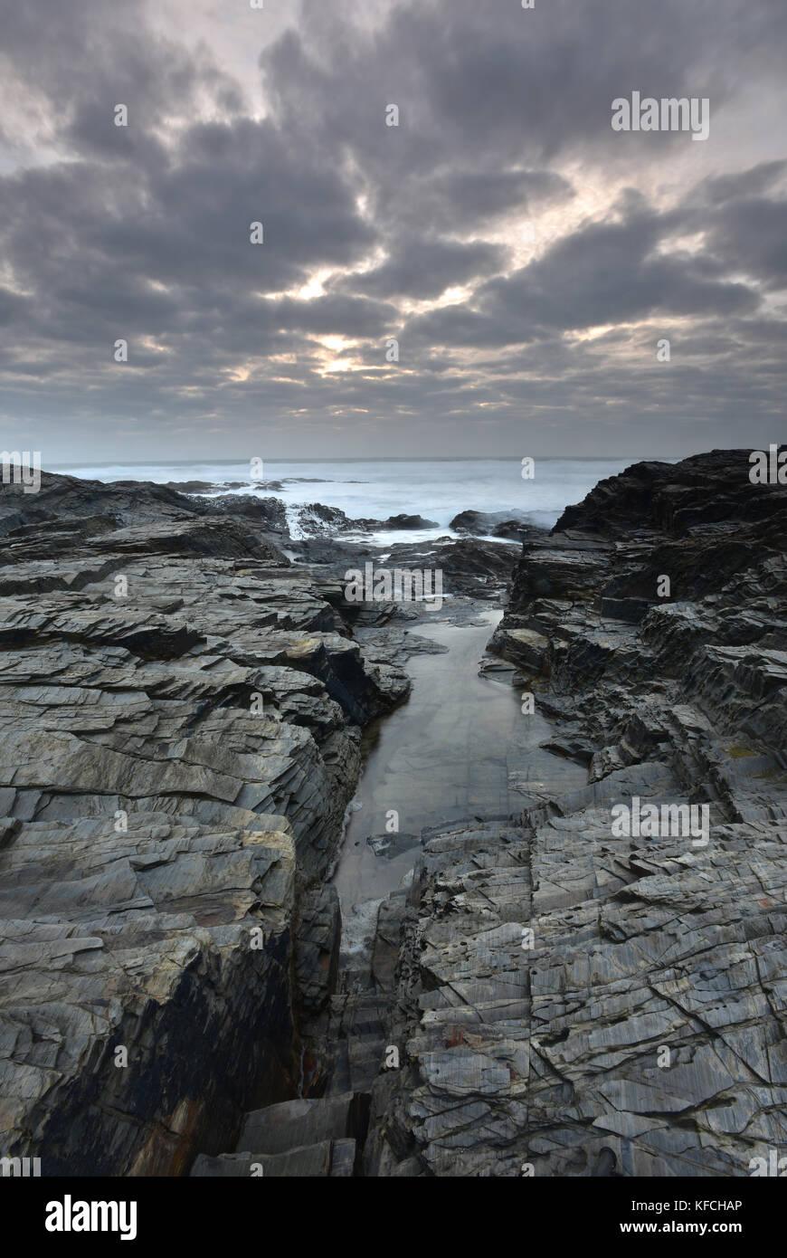 Le rocciose e frastagliate a pressione atmosferica Cornish Coast su una burrascosa serata al Tramonto in Cornovaglia. Immagini Stock