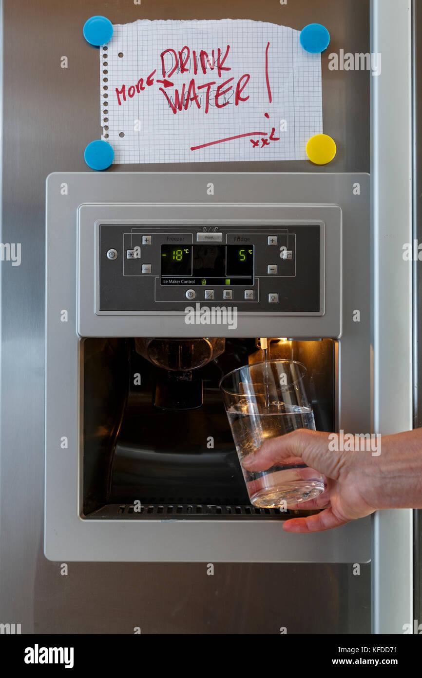 Una mano che tiene un bicchiere sotto il dispenser acqua di uno ...