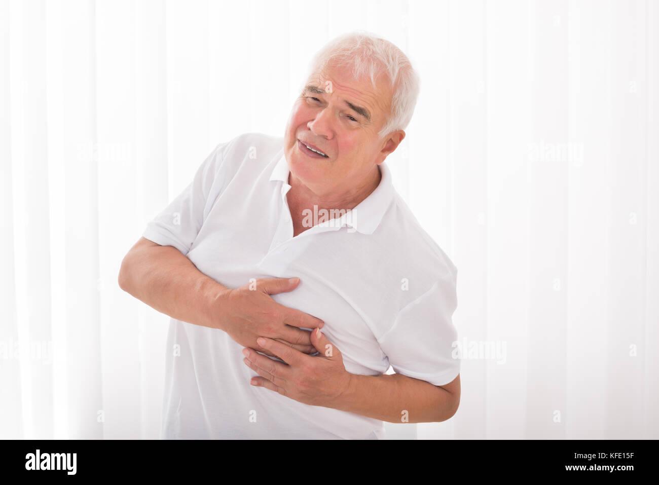 L'uomo con la mano sul petto che soffre di un attacco di cuore Immagini Stock