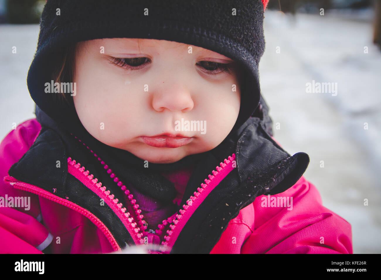 Bambino in piedi nella neve indossando abiti invernali Immagini Stock