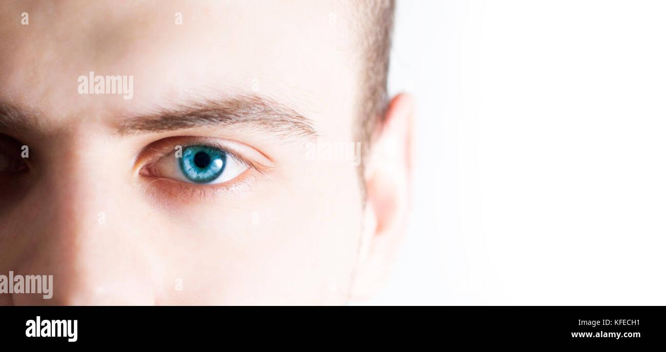 L'uomo guarda la fotocamera, su uno sfondo bianco, metà faccia, con occhio azzurro Immagini Stock