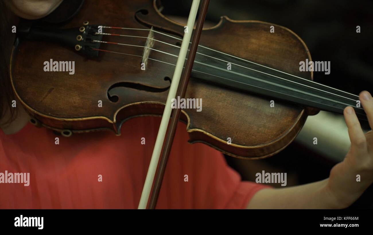 La mano della bambina sulle corde di un violino. la mano della bambina sulla tastiera violino. Immagini Stock