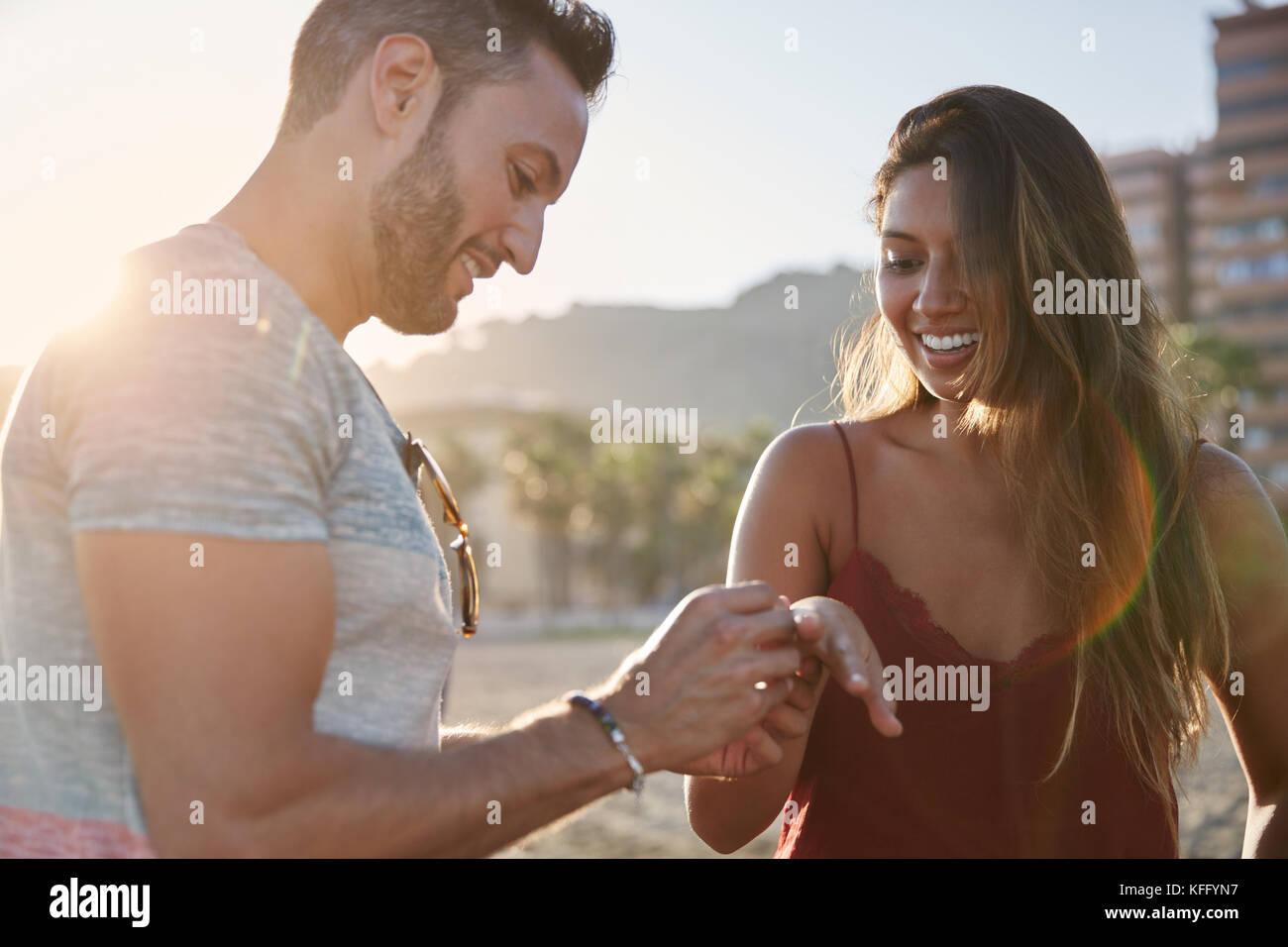 Ritratto di uomo felice mettendo anello di fidanzamento sulla ragazza dito Immagini Stock