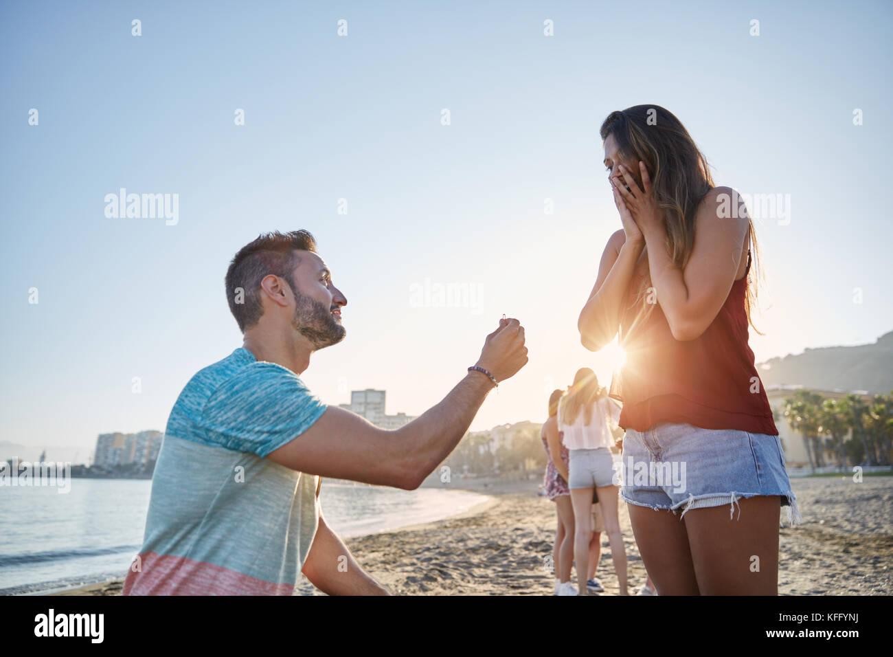 Ritratto di giovane uomo propone alla sua ragazza sulla spiaggia Immagini Stock