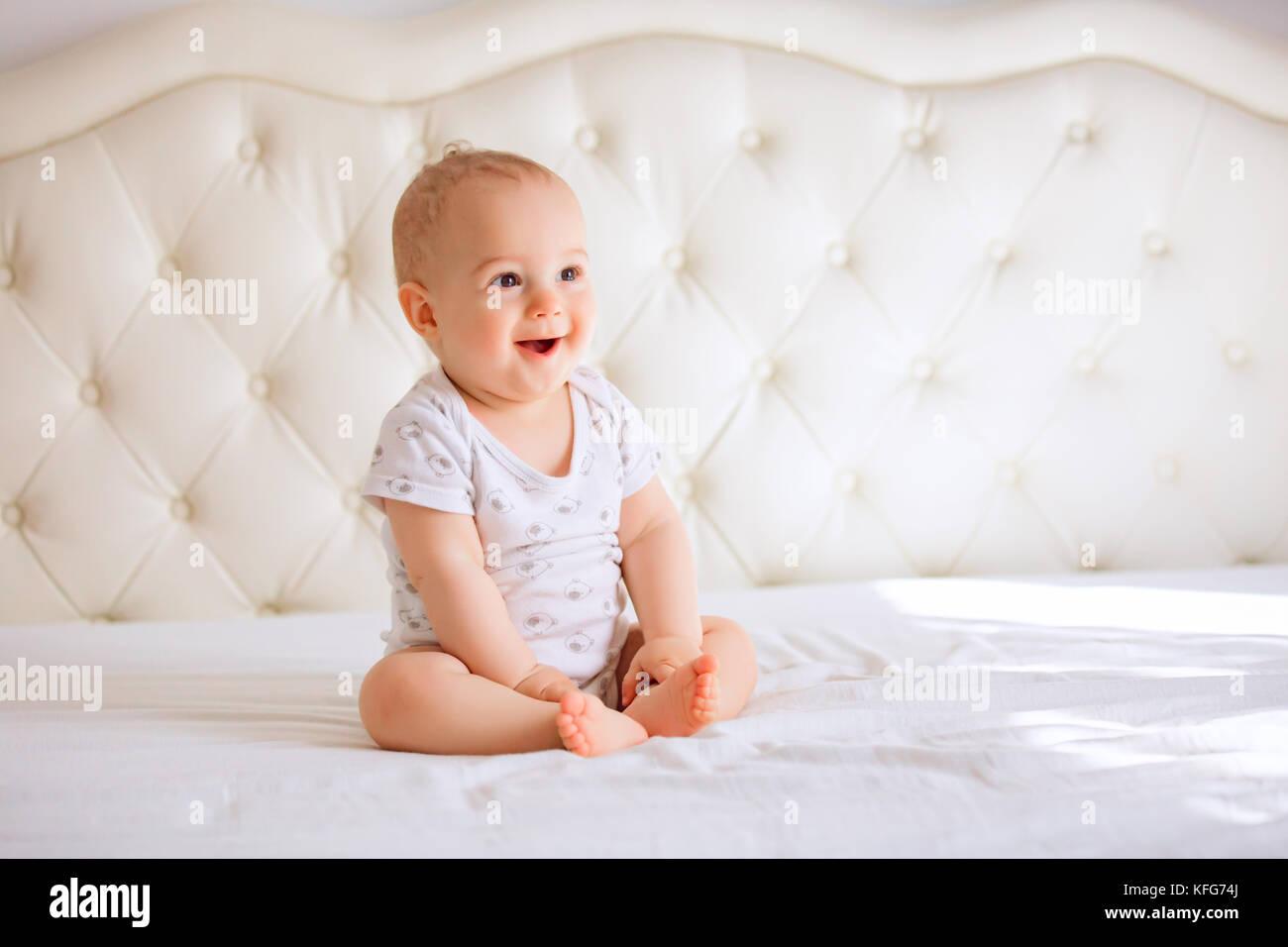 Adorable baby boy in bianco e luminosa camera da letto. Bambino neonato relax nel letto. Scuola materna per i bambini Immagini Stock