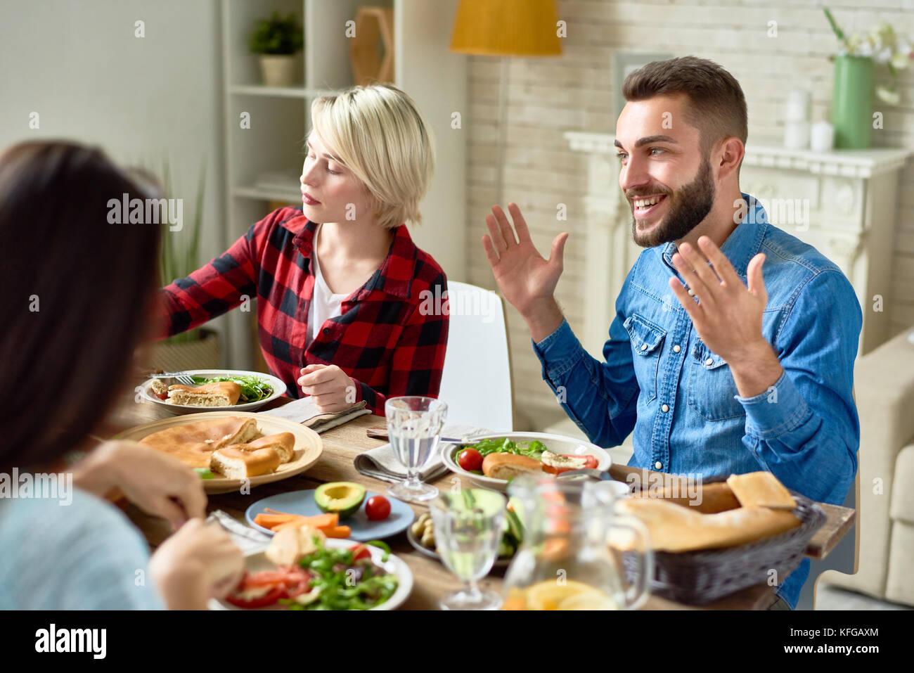 Uomo felice raccontare storie al tavolo per la cena Immagini Stock