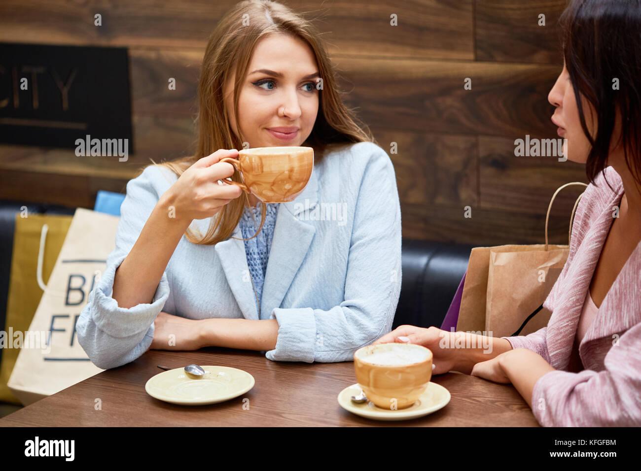 Giovani donne in cafe al centro per lo shopping Immagini Stock
