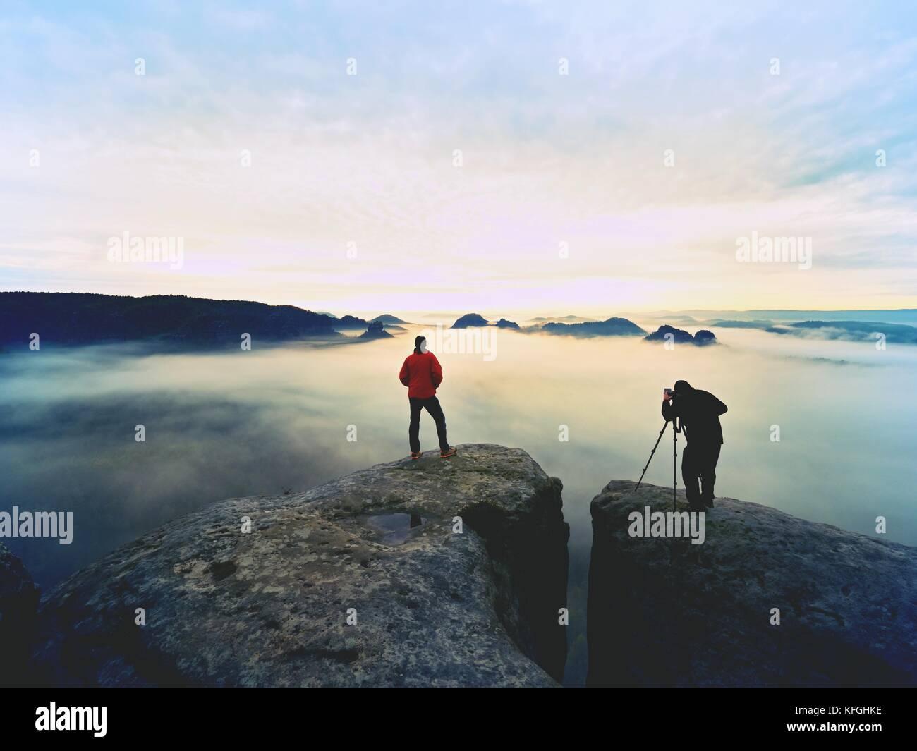 Sagome di uomo fotografi. gli uomini sulla montagna. picco con due uomini di scattare le foto in autunno alba Immagini Stock