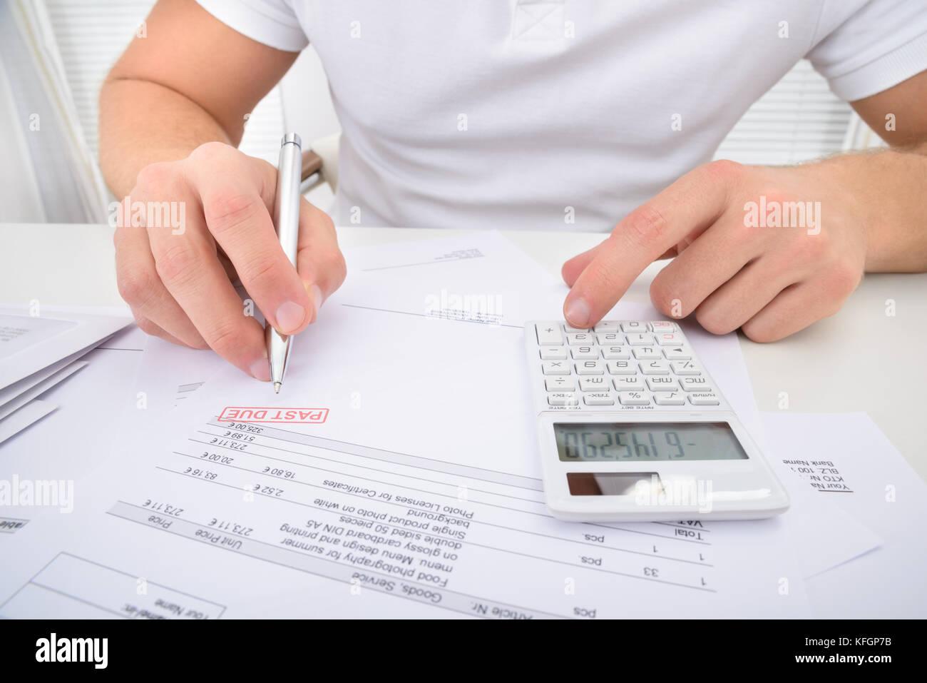 Uomo passato di calcolo a causa dichiarazione utilizzando la calcolatrice Immagini Stock