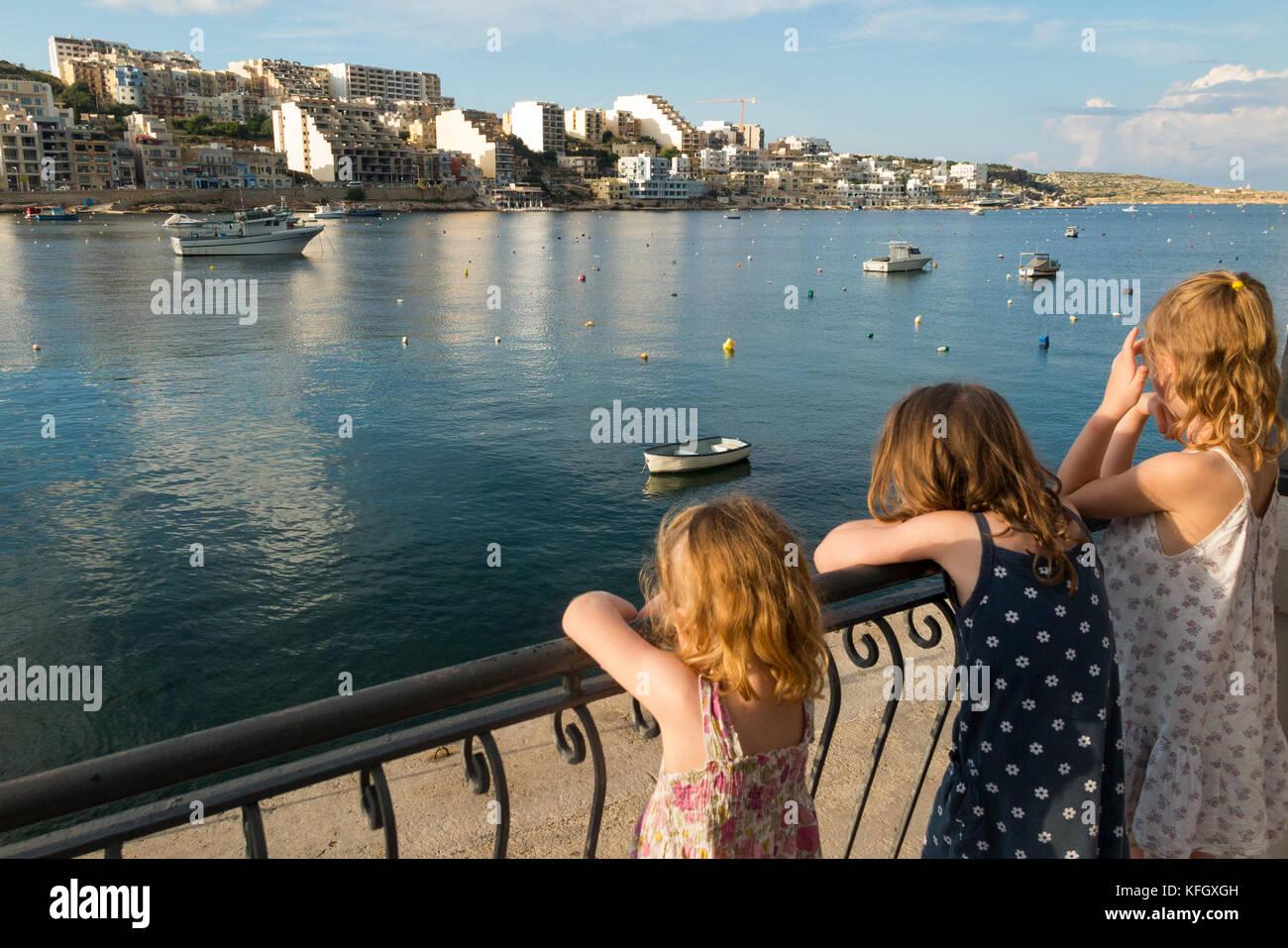 Tre giovani sorelle / ragazze / ragazzi / Kids / kid guardano sulla baia di San Paolo / St Paul s Bay / Xemxija Immagini Stock