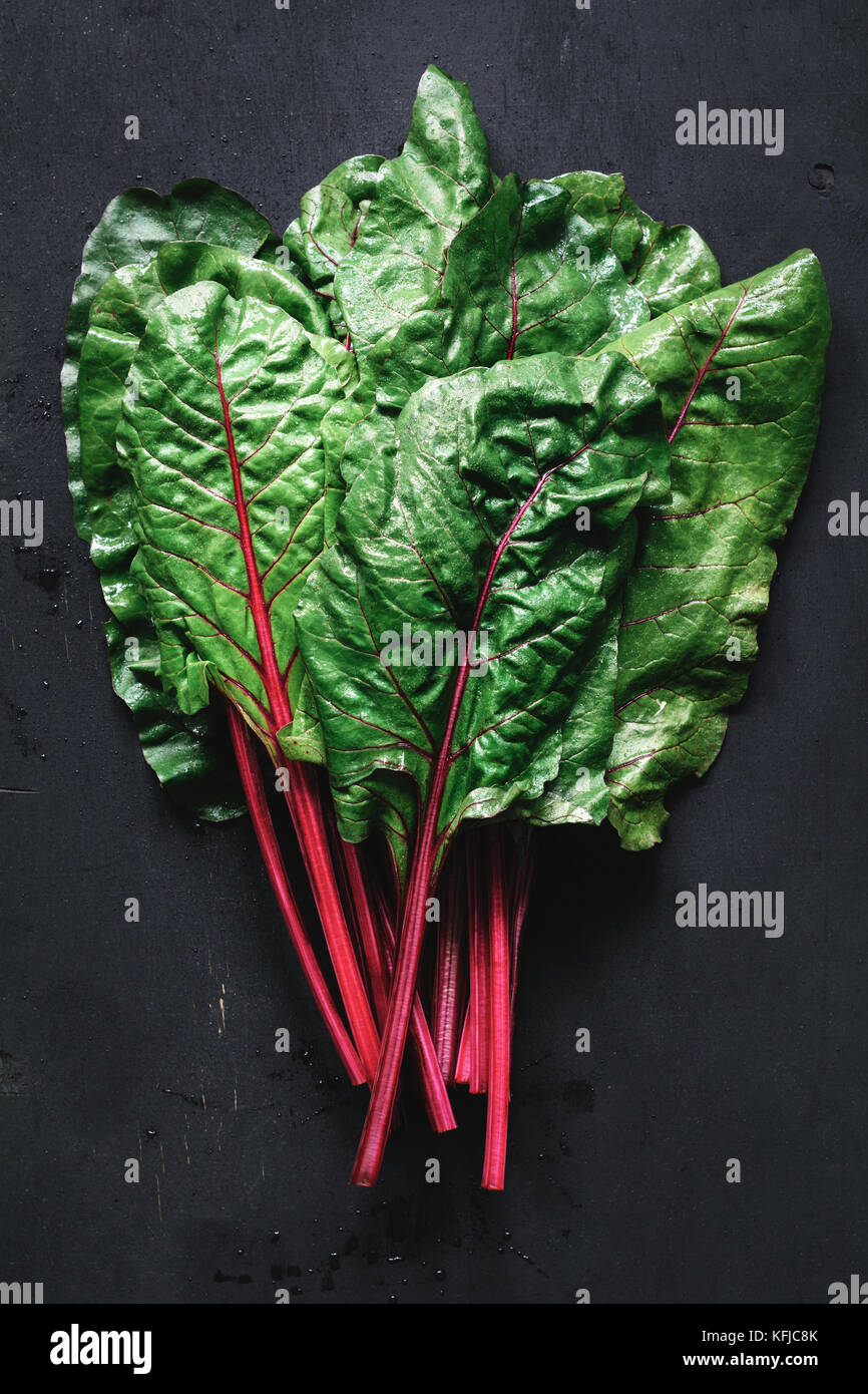 Fresche erbette foglie su sfondo nero. tabella vista superiore organico fresco cibo verde Immagini Stock