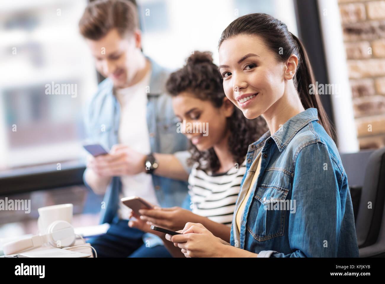 Sorridente ragazza seduta e tenendo premuto il suo telefono Immagini Stock
