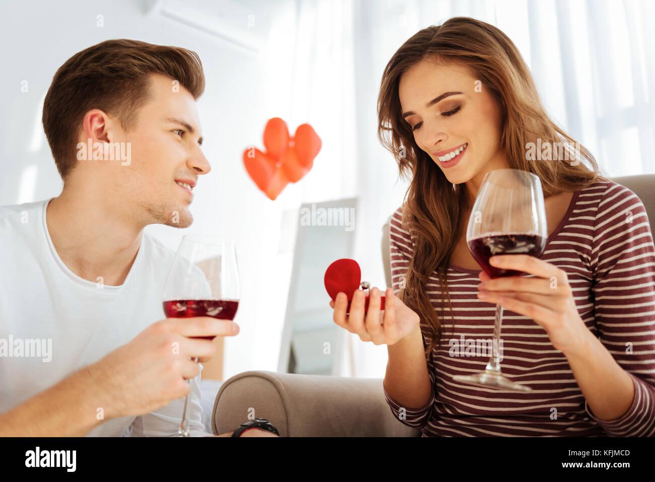 Stupiti giovane lady guardando anello di fidanzamento Immagini Stock