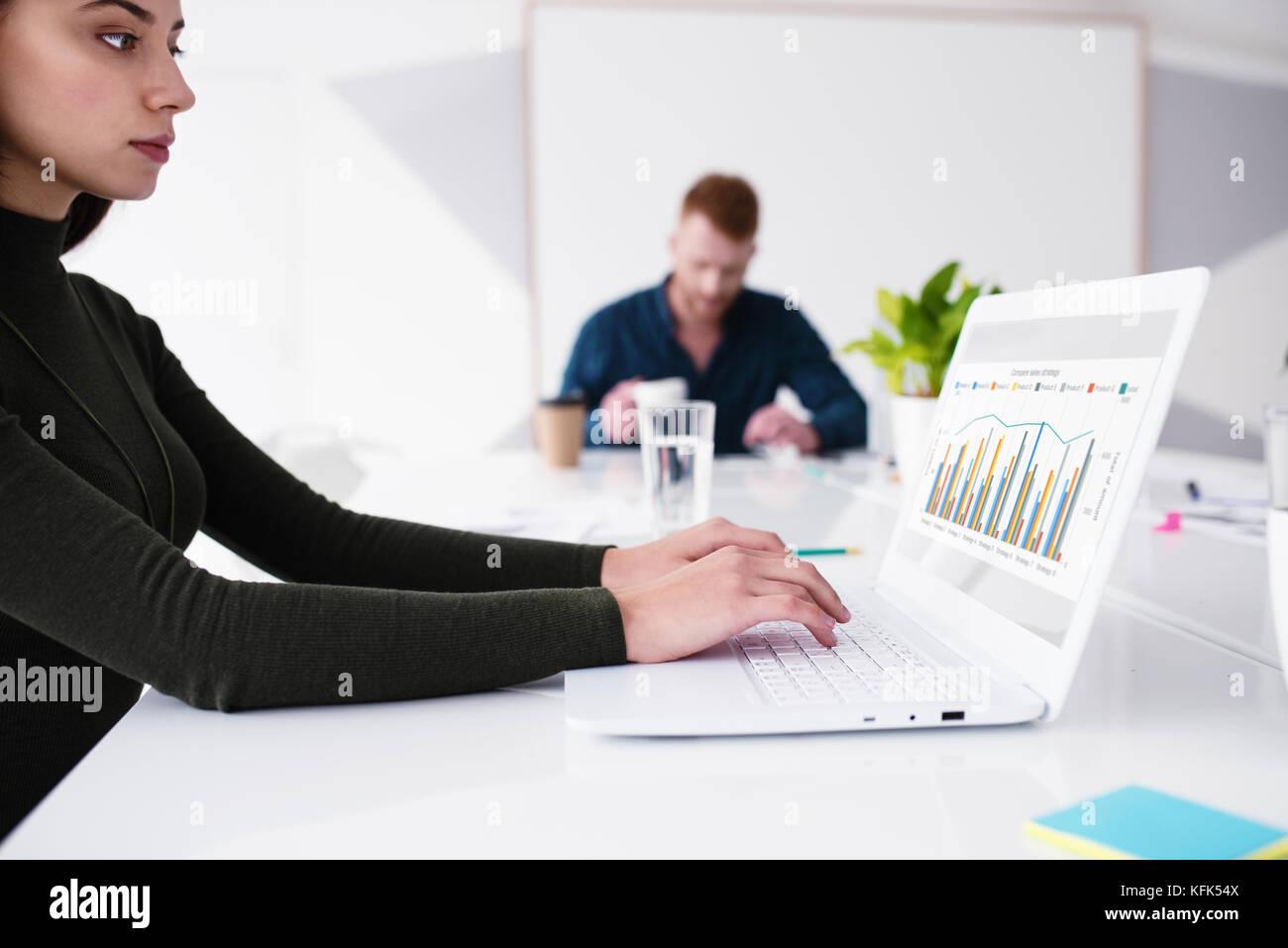 Ragazza funziona su un computer portatile con statistiche dell'azienda. concetto di condivisione internet e Immagini Stock