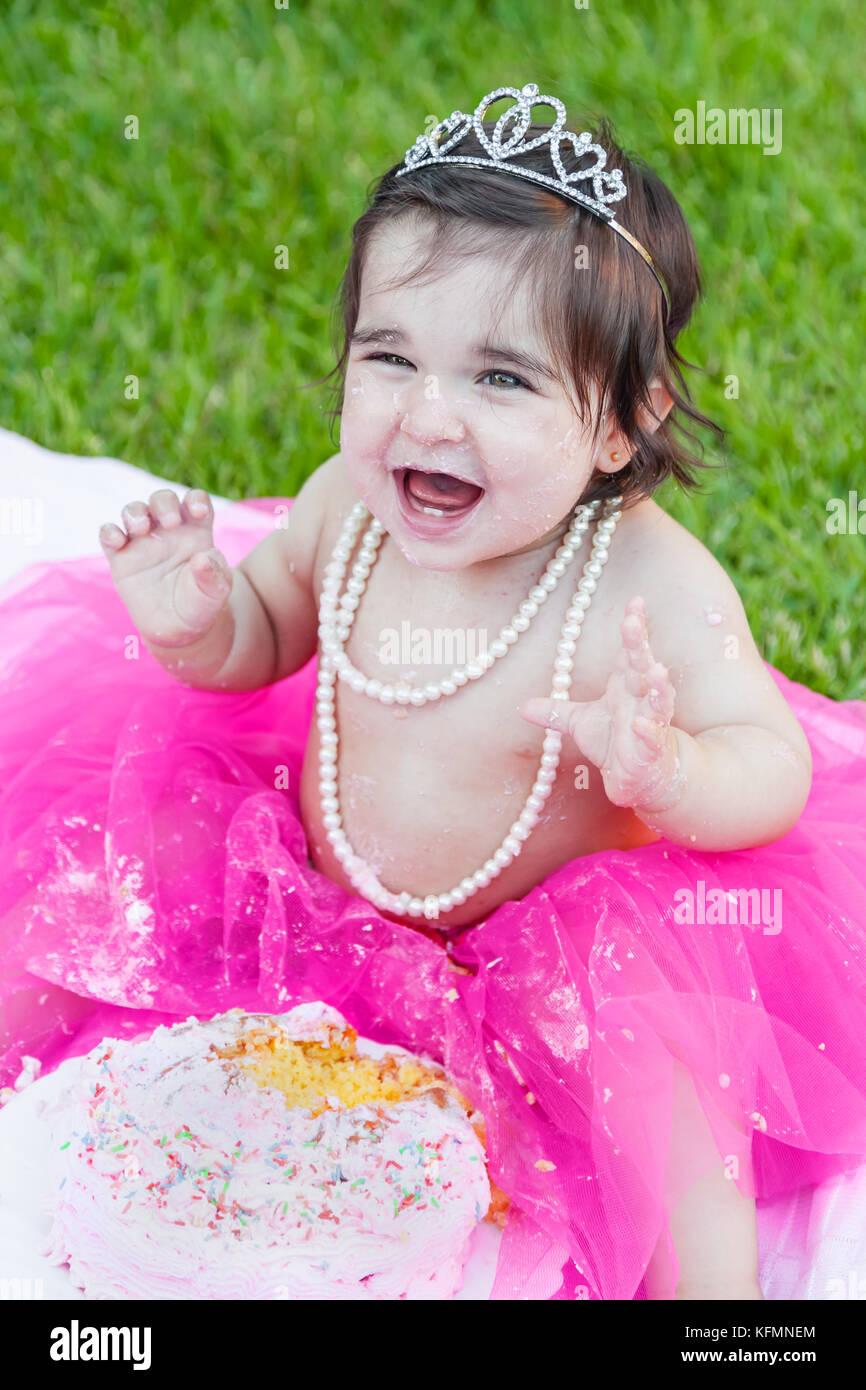 Sorridente happy baby toddler girl primo compleanno festa anniversario. estasiato e ridere, alzare le mani, il viso Immagini Stock
