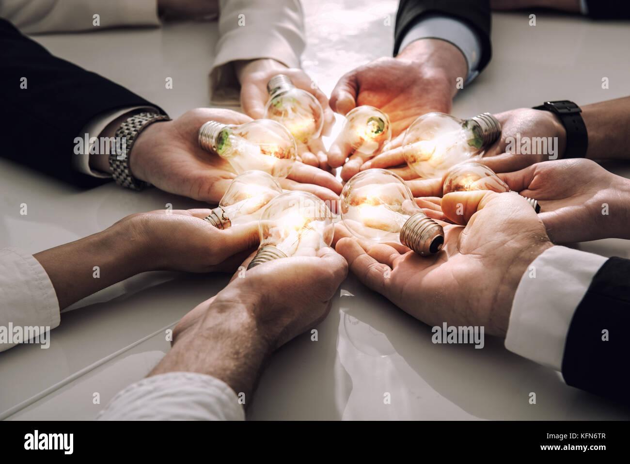 Il lavoro di squadra e il concetto di brainstorming con gli imprenditori che condividono un'idea con una lampada. Immagini Stock