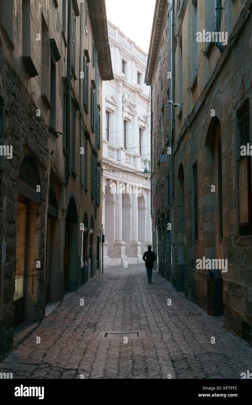 SILHOUETTE di un uomo che cammina su un deserto strada stretta. Città Alta (città alta), Bergamo, Lombardia, Immagini Stock