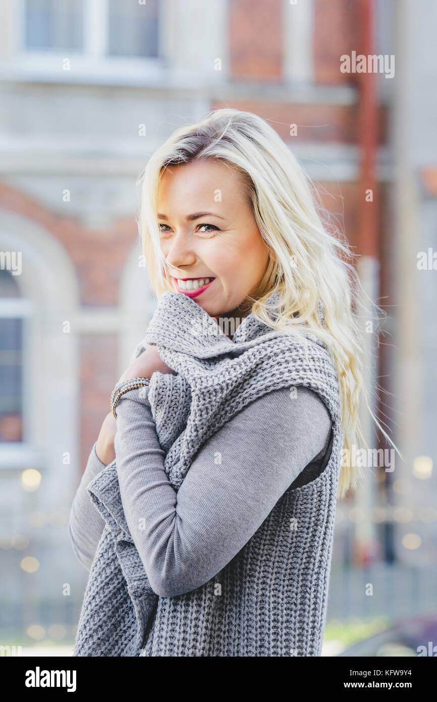 04974ded685b Elegante giovane donna bionda che indossa cardigan grigio camminando sulla  vecchia strada di città. moda casual