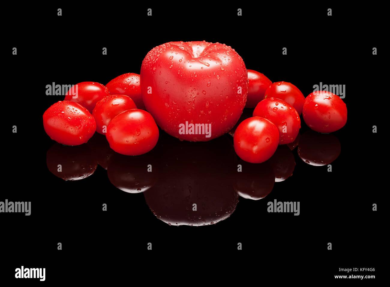 Un Unico Grande Tutto Rosso E Un Mucchio Di Pomodorini Isolato Nero