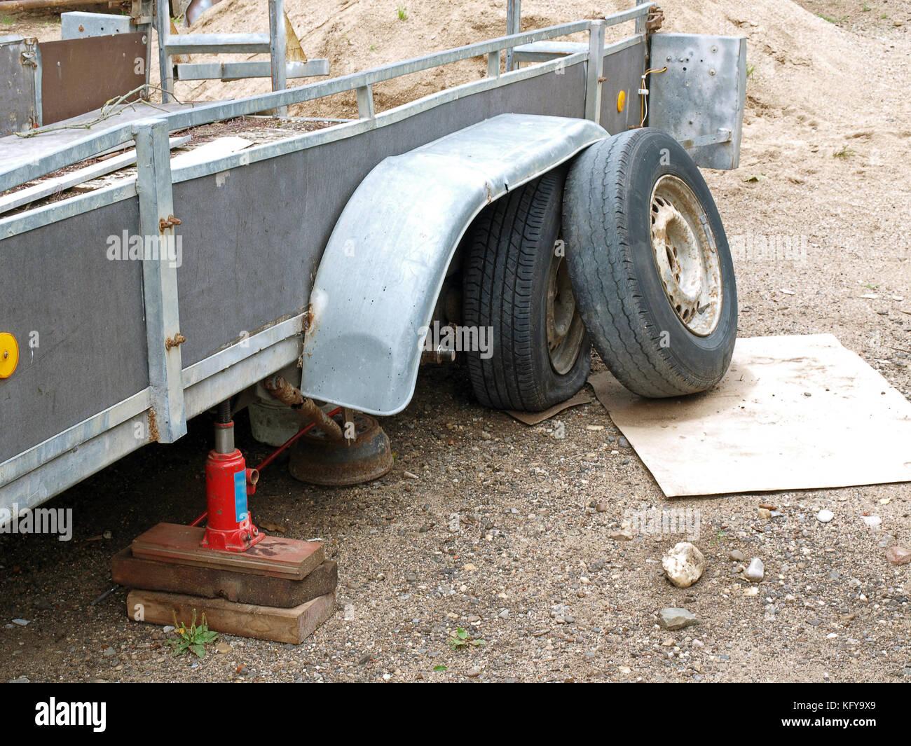 Danneggiato Il rimorchio con pneumatico sgonfio sollevato sul lato strada Immagini Stock