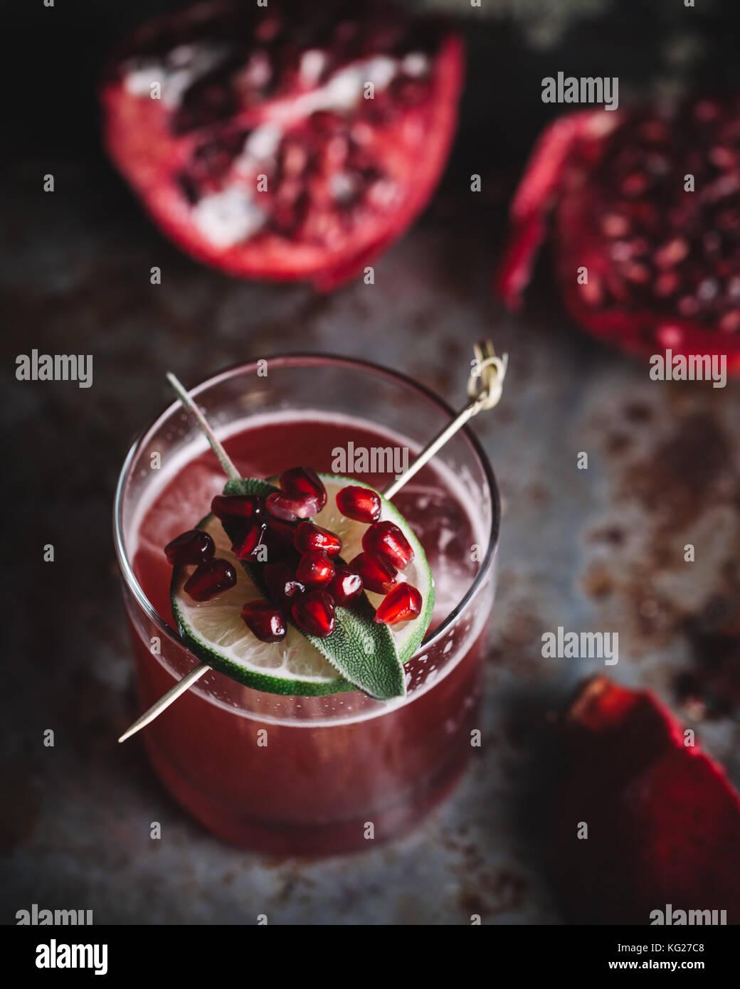 Cocktail alcoolico guarnita con i semi di melograno on dark moody sfondo Immagini Stock